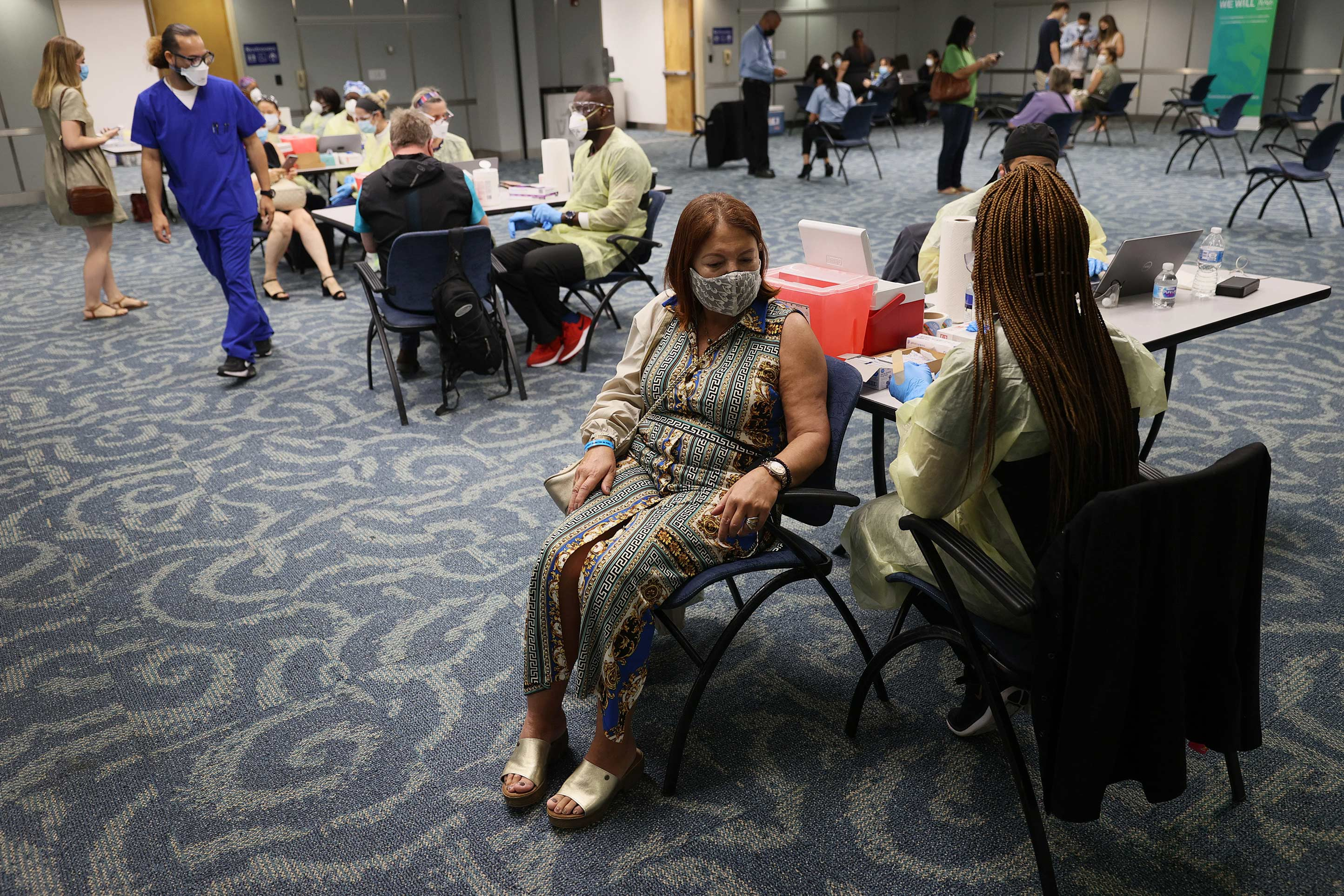 Sylvia March gets a Pfizer-BioNtech COVID-19 vaccination from a health care worker at Miami International Airport on May 10 in Miami.