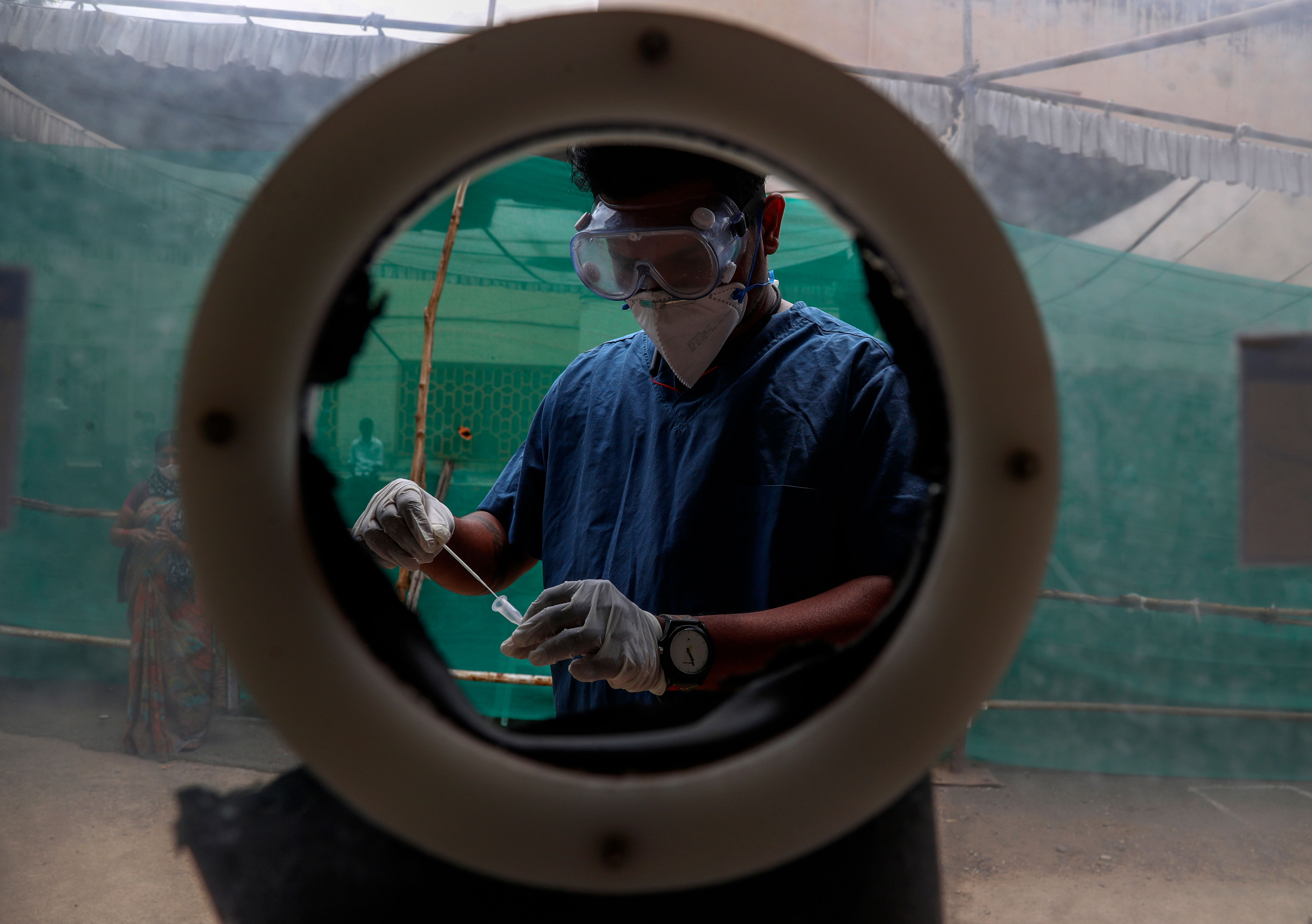 A health worker collects nasal swab samples at a Covid-19 testing center in Hyderabad, India, on April 12.