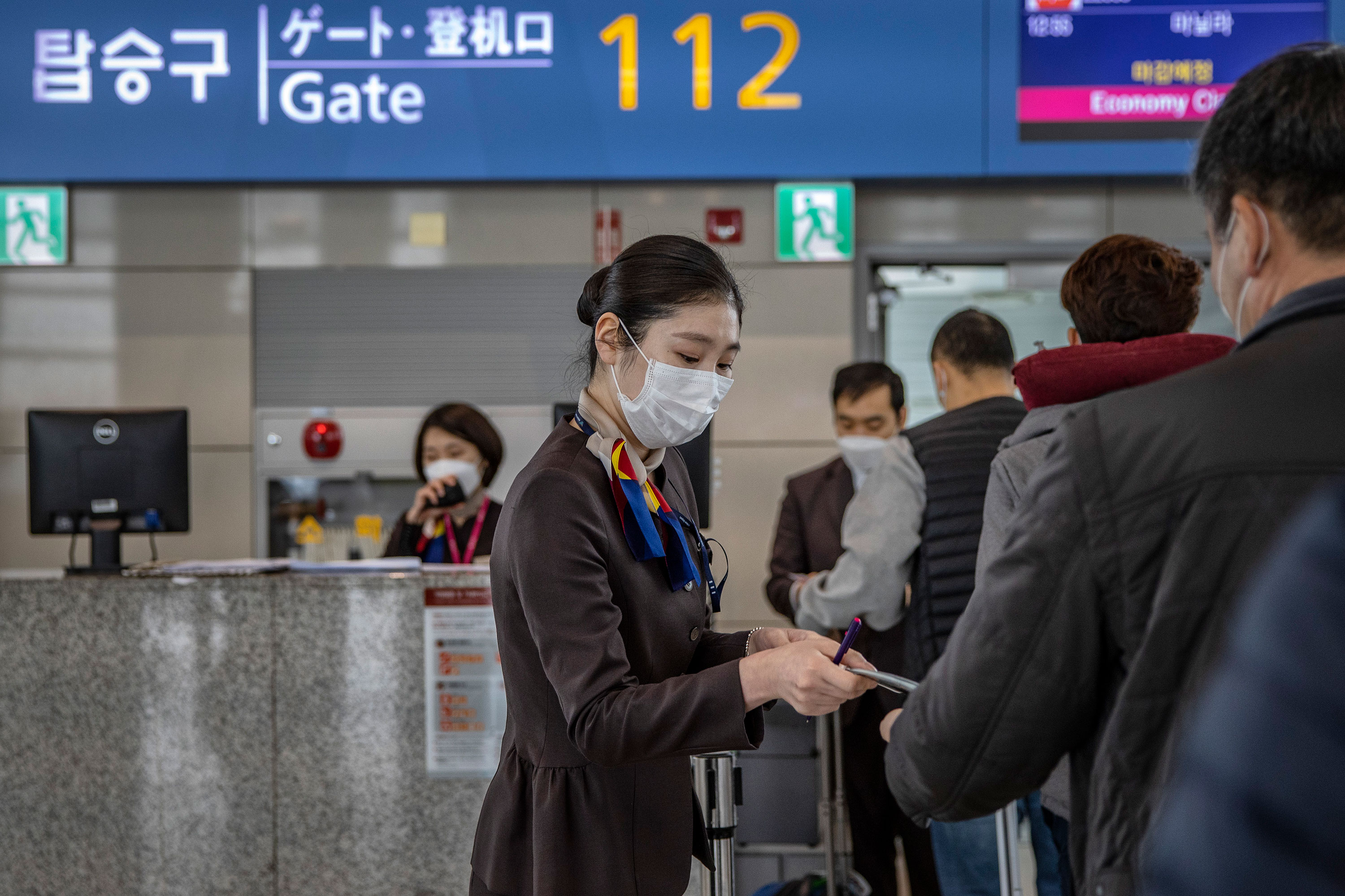 An employee assists passengers at the Incheon International Airport on March 10 in Incheon, South Korea.