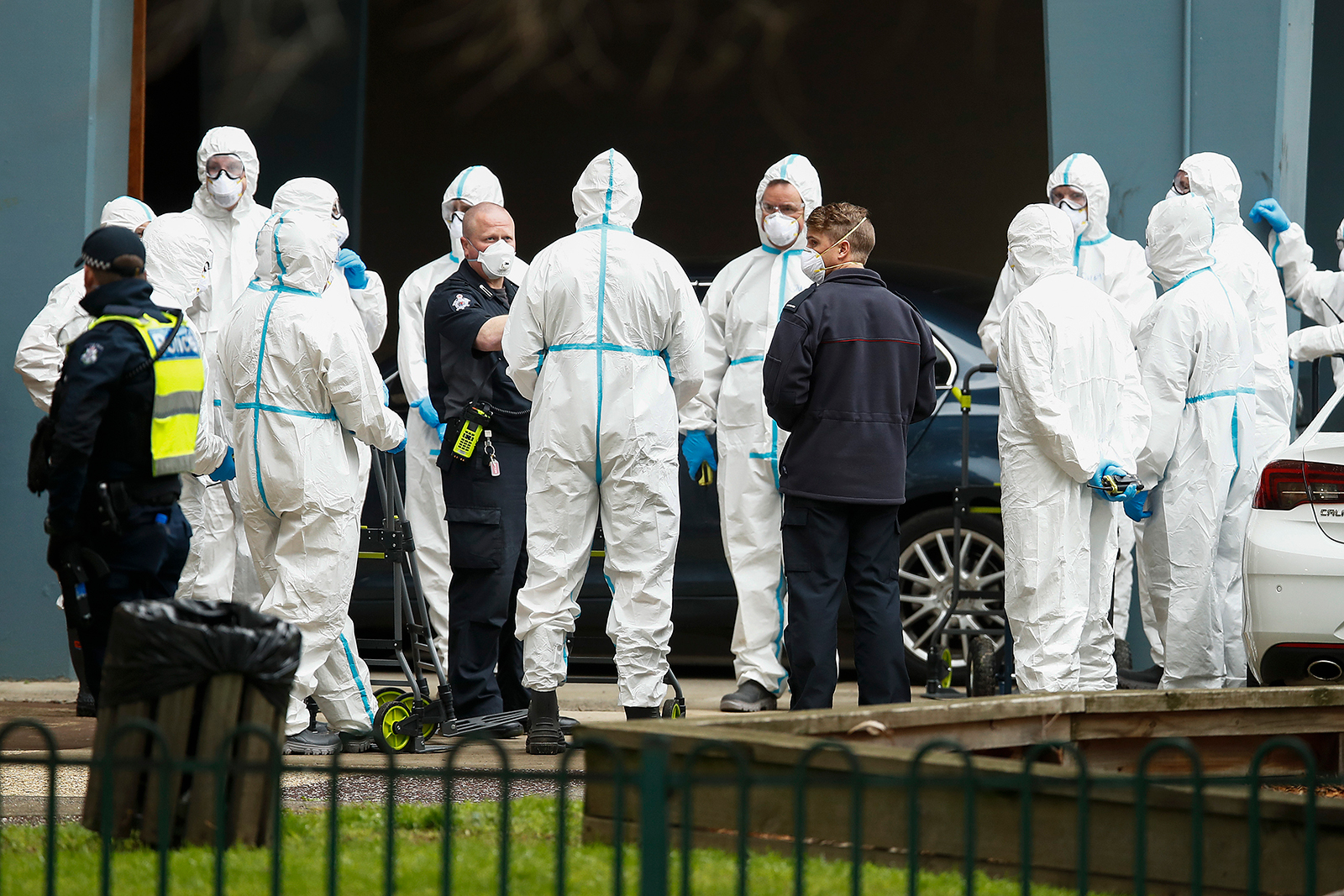 Workers in personal protective equipment are seen, along side police patrols, on July 7, in Melbourne, Australia.