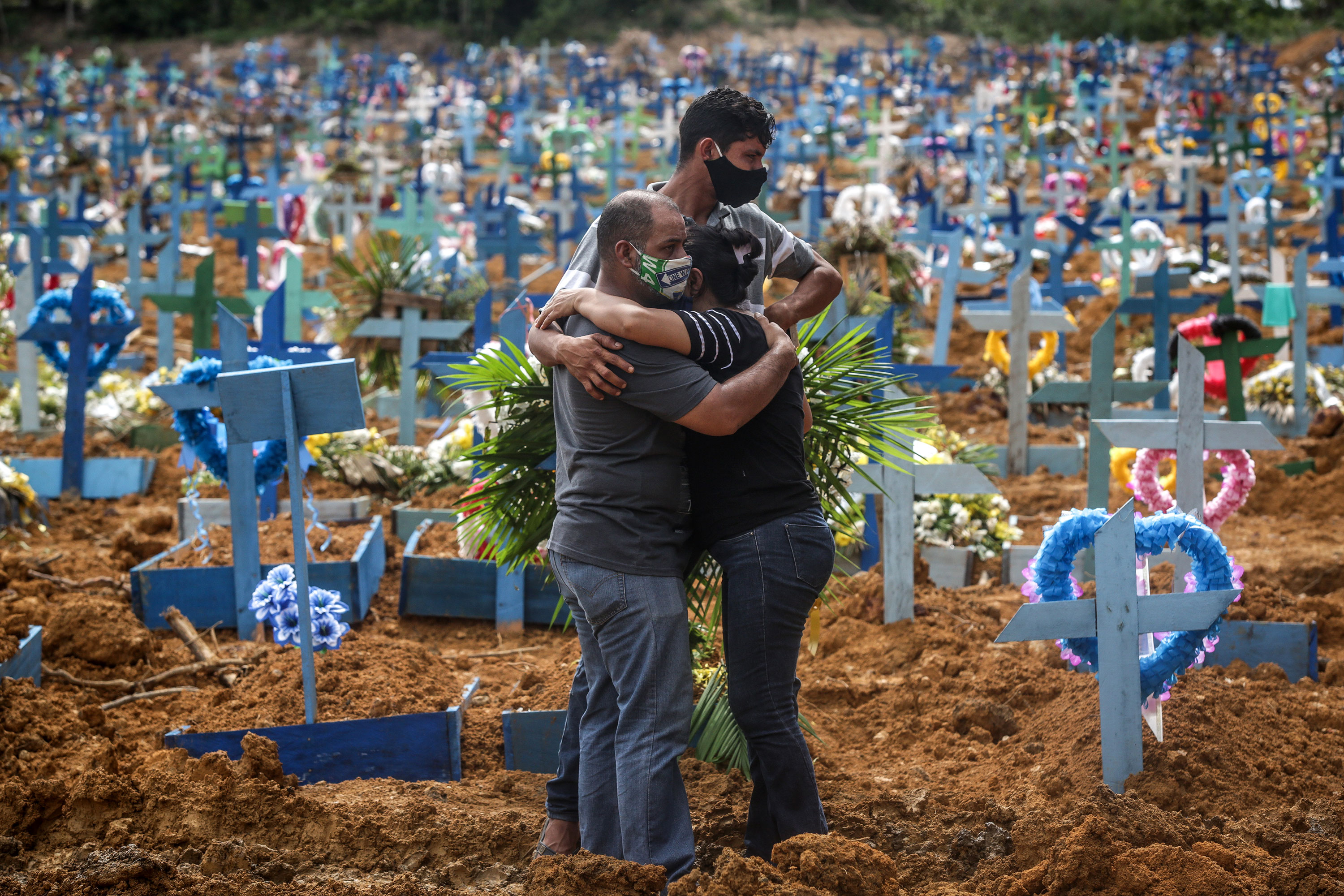 People mourn during a mass burial of coronavirus victims at the Parque Taruma cemetery in Manaus, Brazil, on May 19.