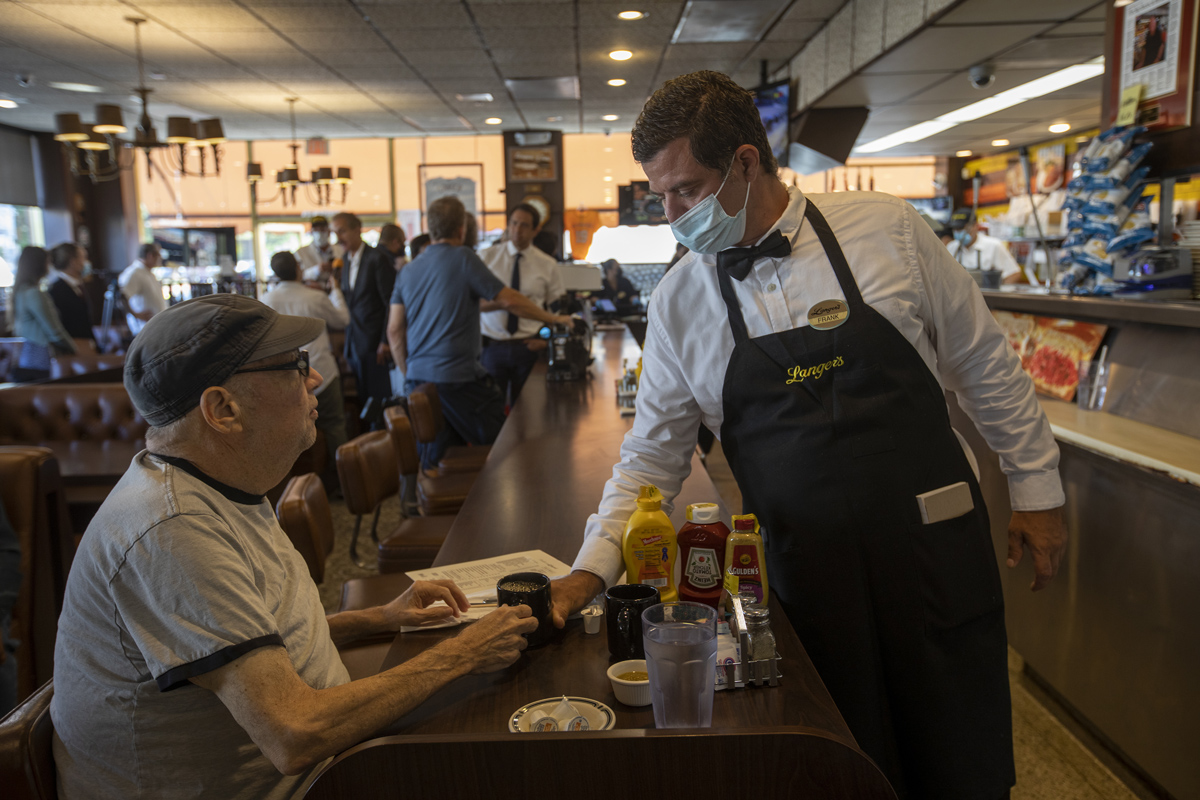 A masked server waits on a customer at Langer's Deli in Los Angeles, California on June 15.
