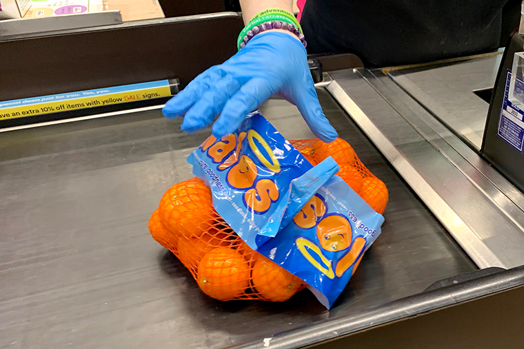 A cashier wears gloves on March 23, 2020 in Cambridge, Massachusetts.