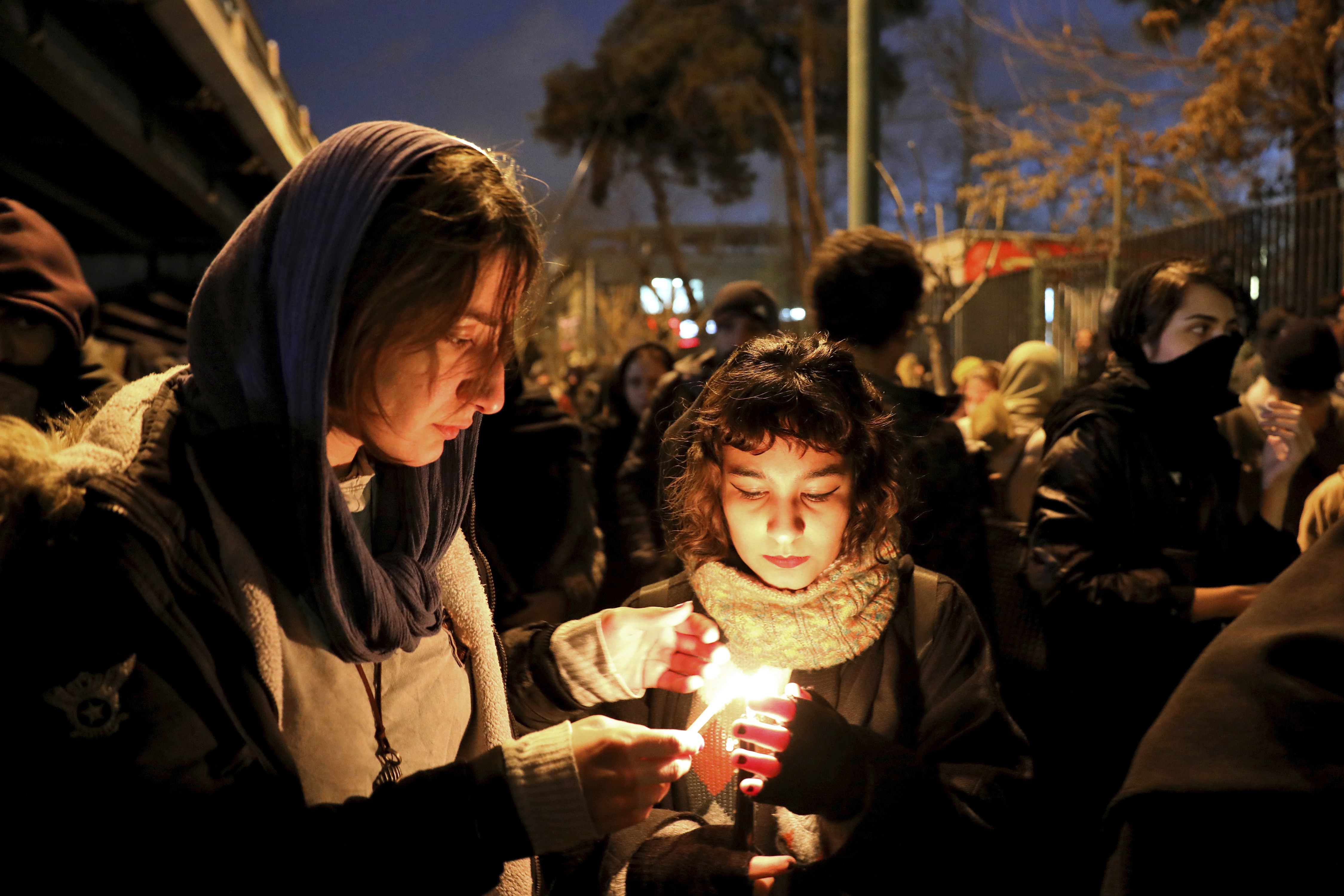 People gather for a candlelight vigil to remember the victims of the Ukraine plane crash in Tehran, Iran, on Saturday, January 11.