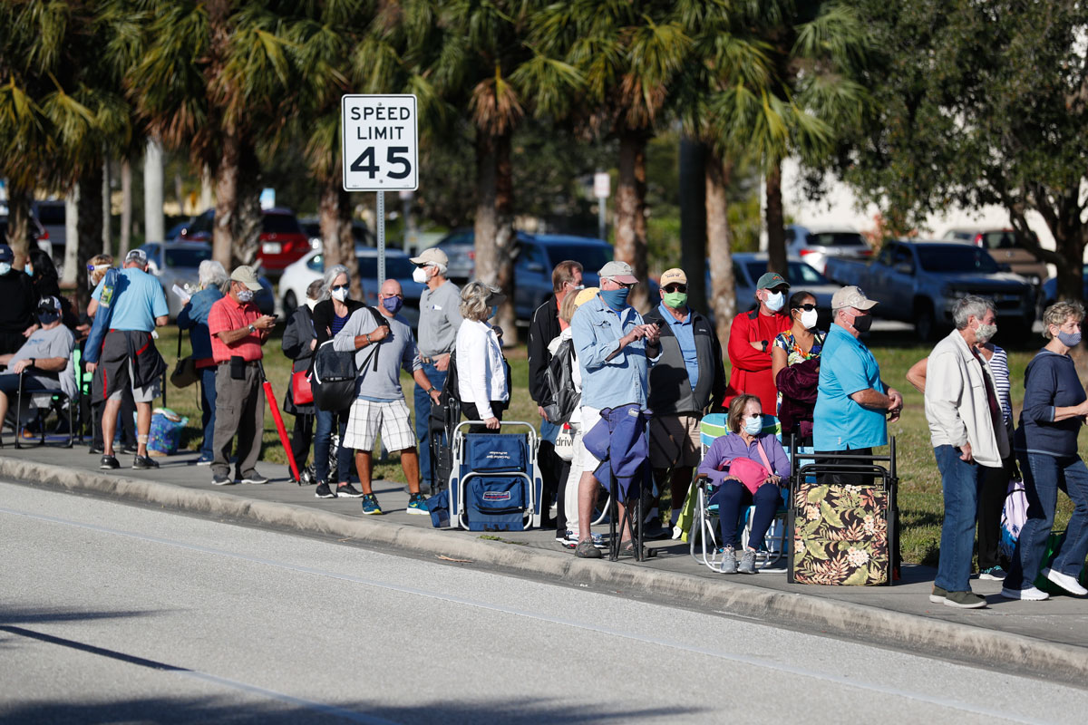 Seniors and first responders wait in line to receive a Covid-19 vaccine at the Lakes Regional Library on December 30, 2020 in Fort Myers, Florida.