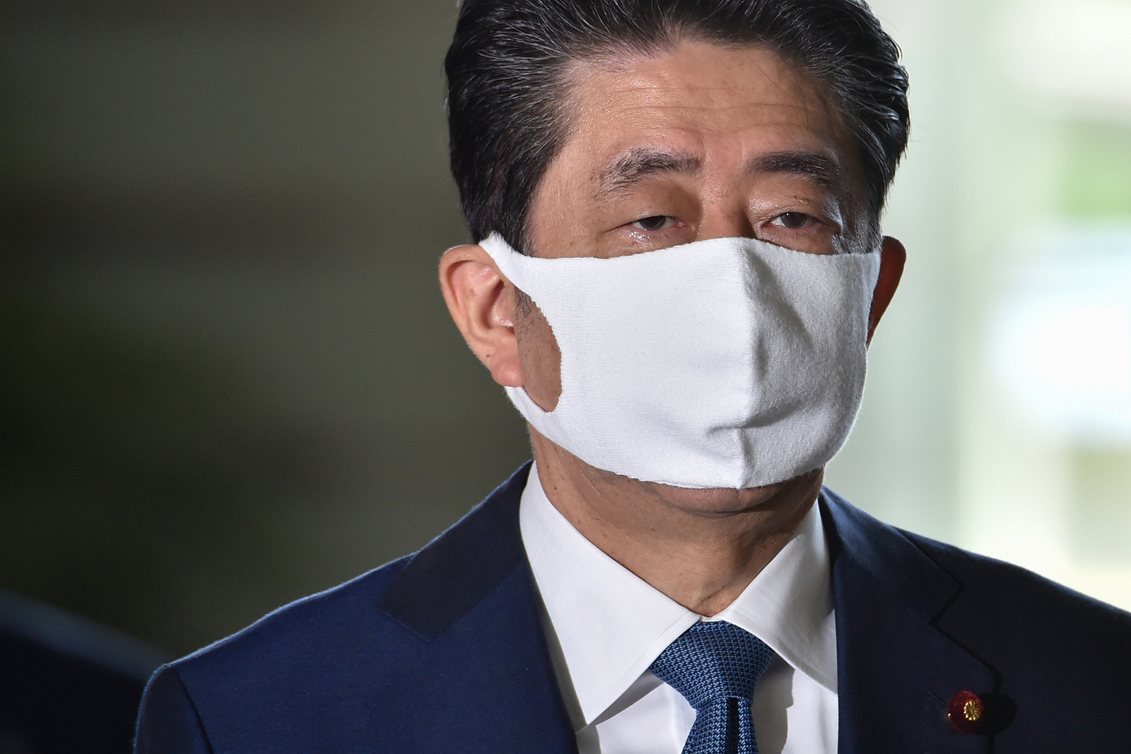 Japan's Prime Minister Shinzo Abe wearing a face mask arrives at the prime minister's office in Tokyo, on August 28.
