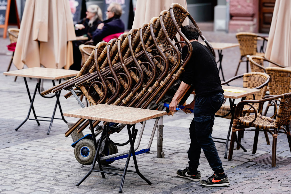 The employee of a pub rolls a stack of chairs onto the market place in Heidelberg, on May 15, as coronavirus restrictions starts to loosen in parts of Germany.