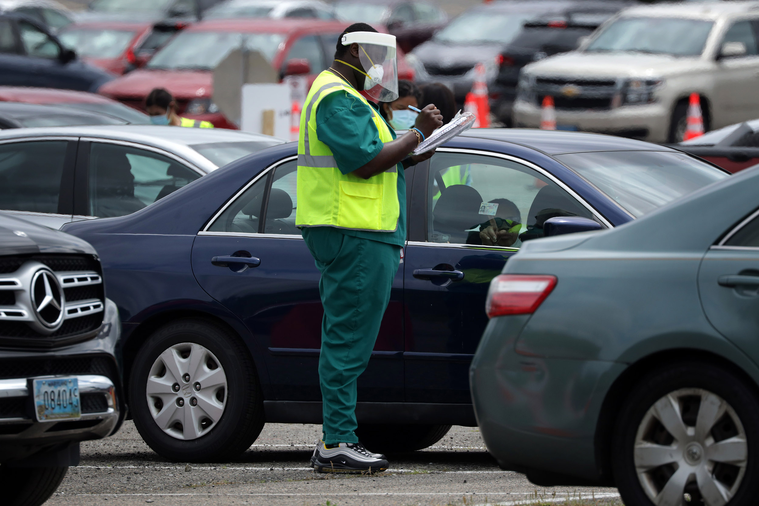 A worker collects information from local residents as he check them in at a drive-thru coronavirus testing location at Six Flags America in Bowie, Maryland, on May 29.