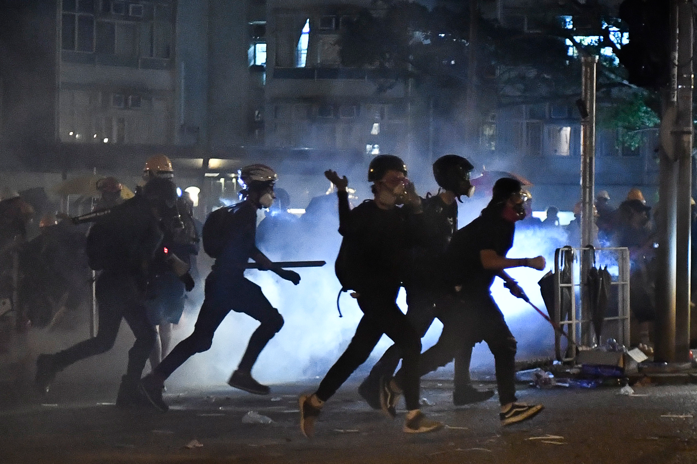 Protesters run as police fire tear gas at them in Wong Tai Sin during a general strike in Hong Kong on August 5.