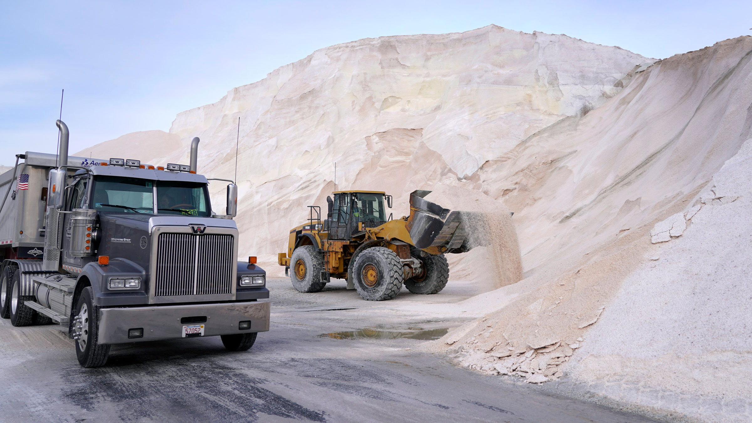 A dump truck in Chelsea, Massachusetts, waits for a front-end loader to pour road salt into it on Wednesday. The salt would be delivered to area municipal depots.