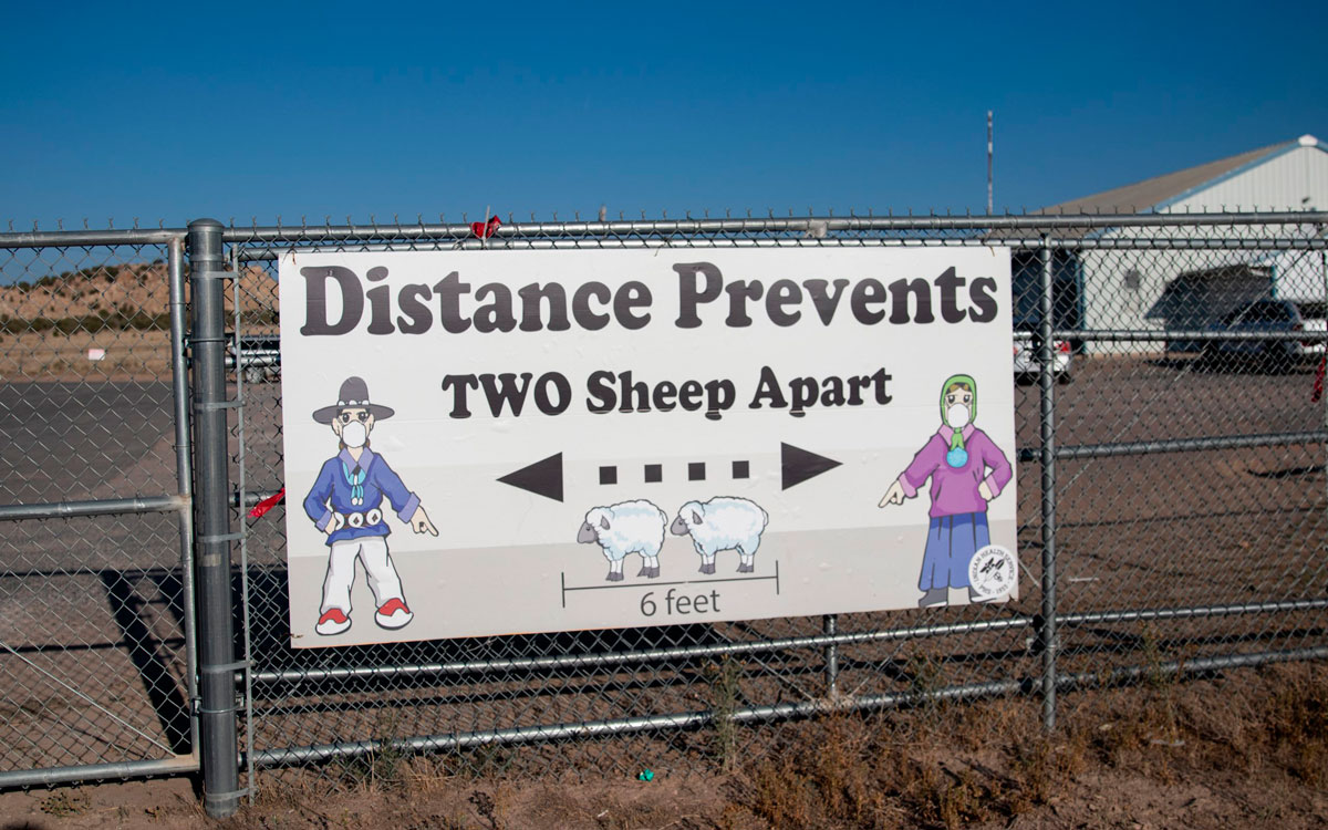 A sign encourages social distancing outside the Blue Gap Mini Store in Blue Gap, Arizona on Sept. 24.