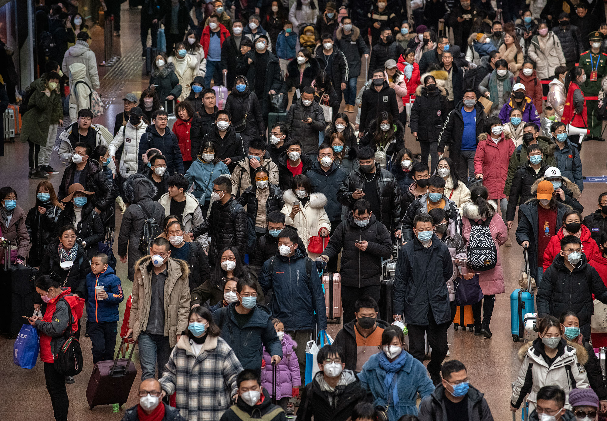 Chinese passengers, most wearing masks, prepare to board trains in Beijing on Thursday, January 23.