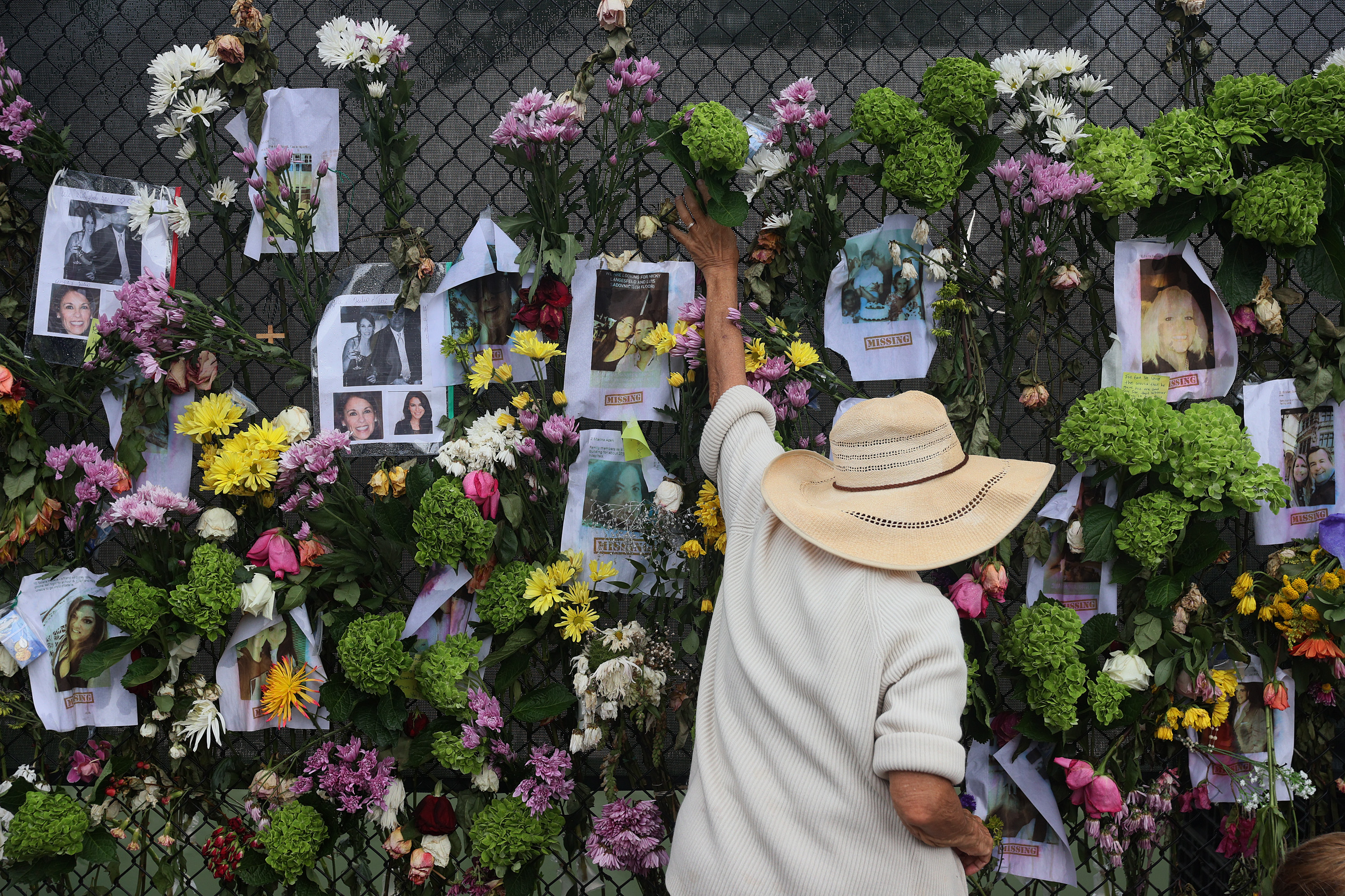 A person adds flowers to a memorial that has pictures of some of the missing from the partially collapsed 12-story Champlain Towers South condo building on June 28, in Surfside, Florida.