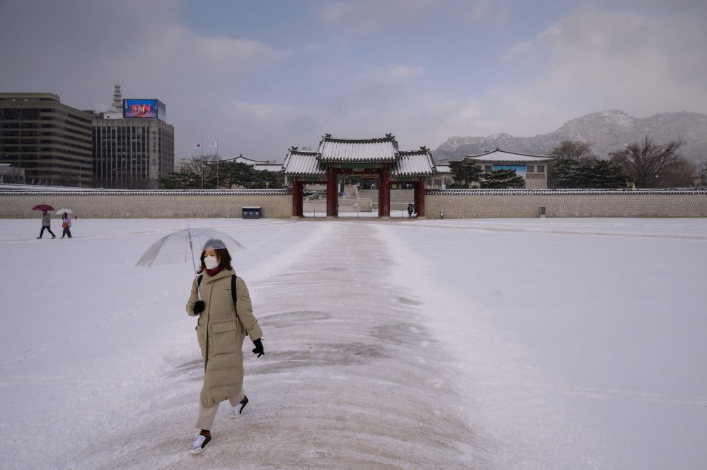 A visitor wearing a protective face mask walks through Gyeongbokgung Palace in Seoul, South Korea on February 17, 2020.