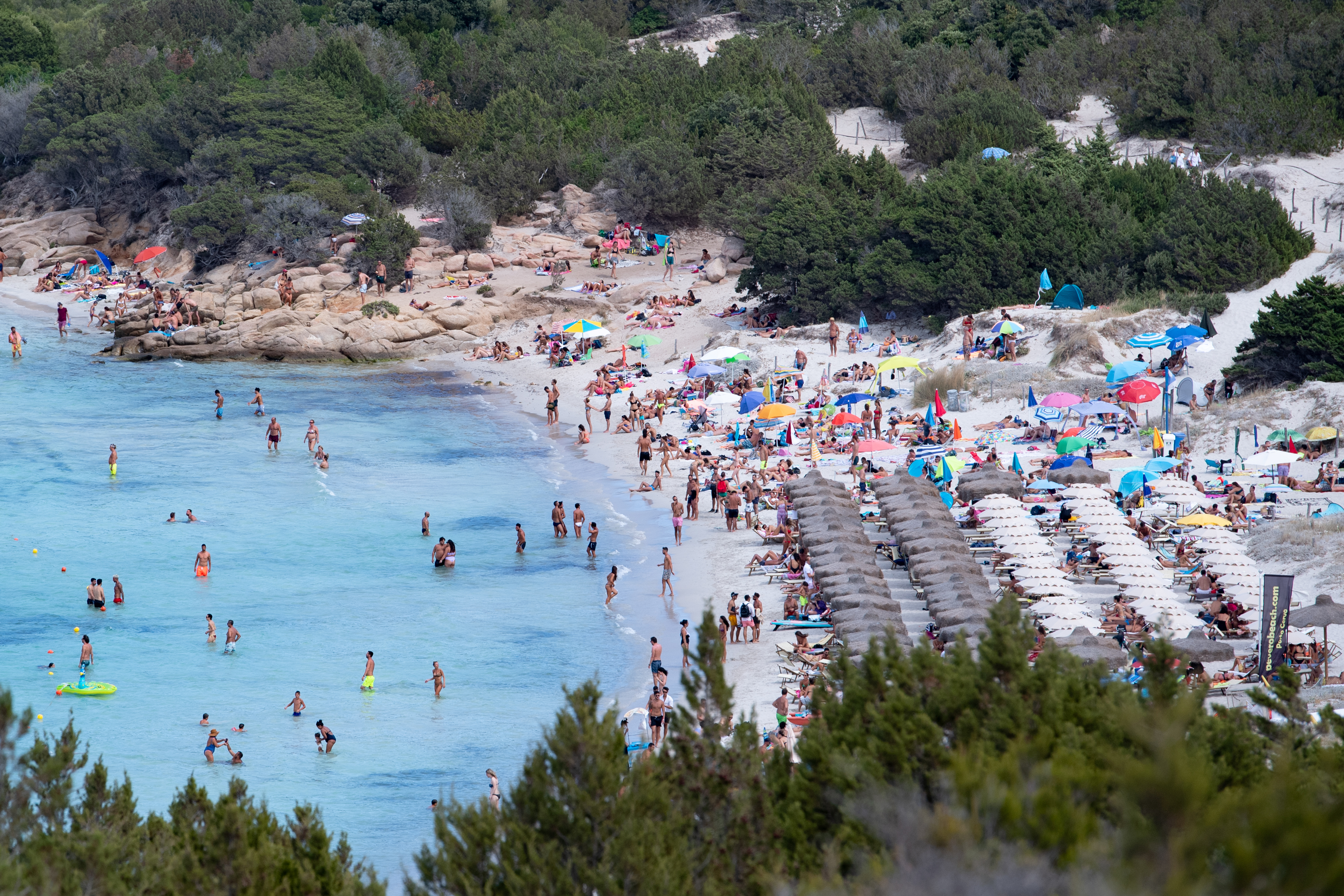 People visit a beach in Porto Cervo, Italy, on August 18.