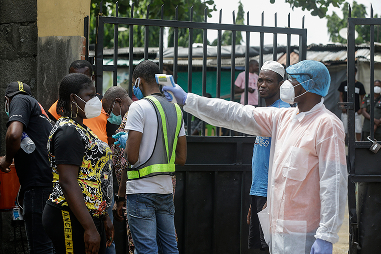 A health official, right, takes the temperature of a patient looking to be tested, before entering a government-run testing centre in Lagos, Nigeria, on Thursday, April 23.