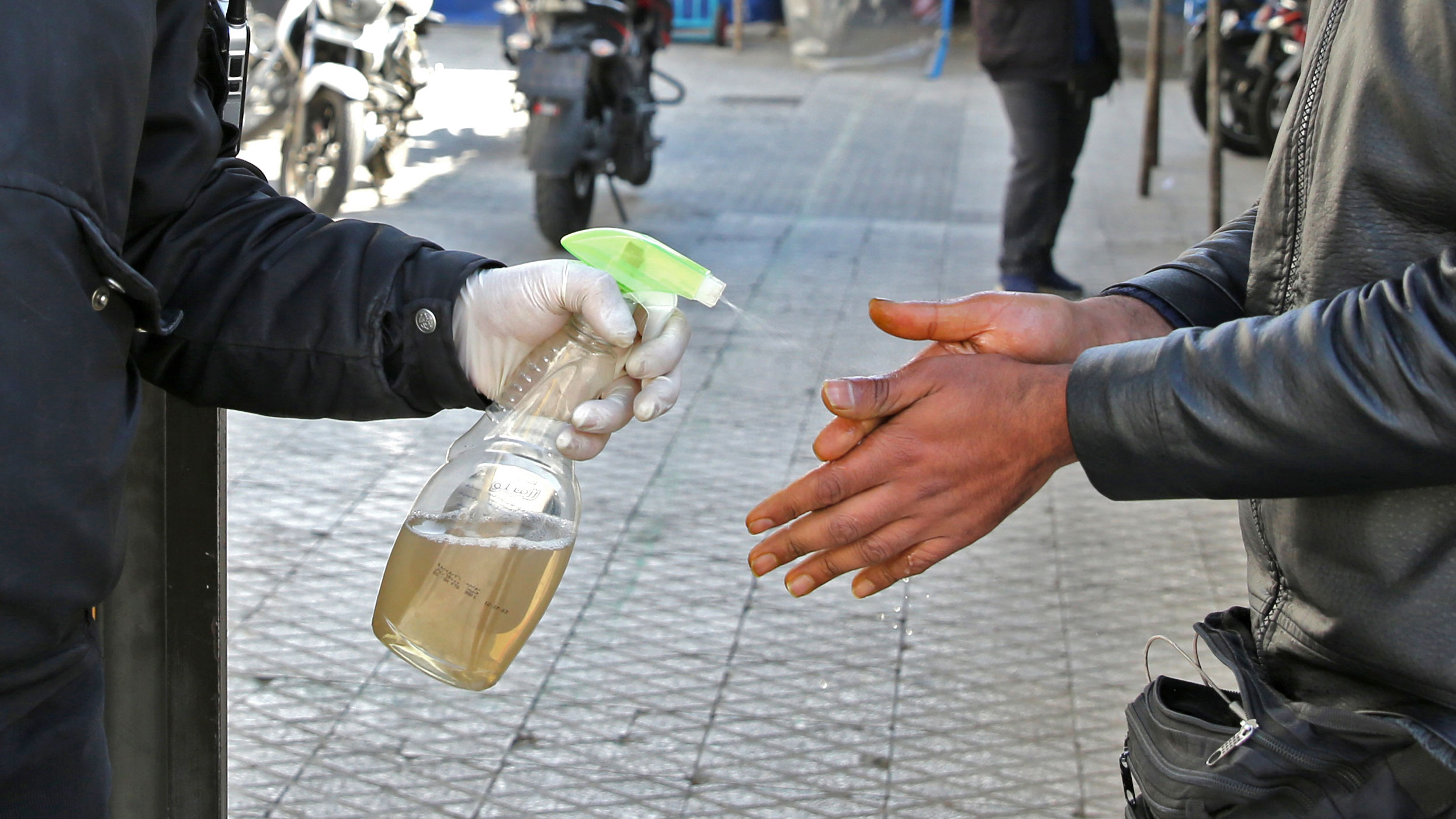 An Iranian man sprays alcohol on the hands of people outside an office building in Tehran on March 4.