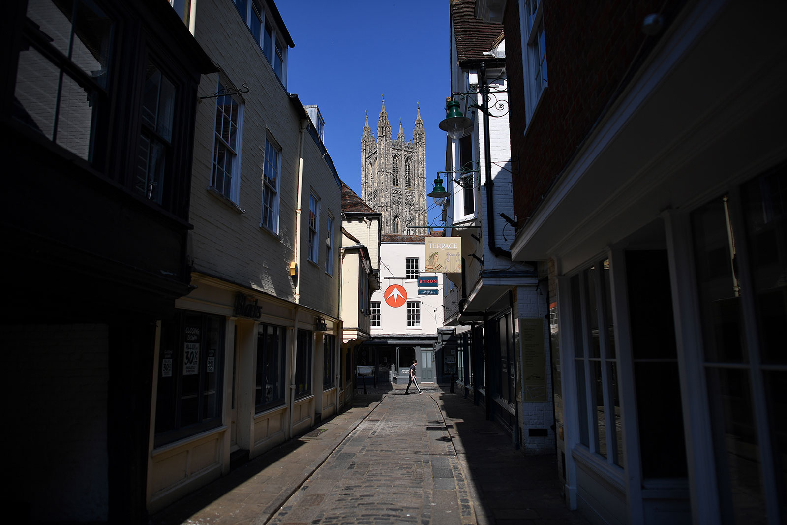 A person walks down a nearly empty street in Canterbury, England, on April 11.