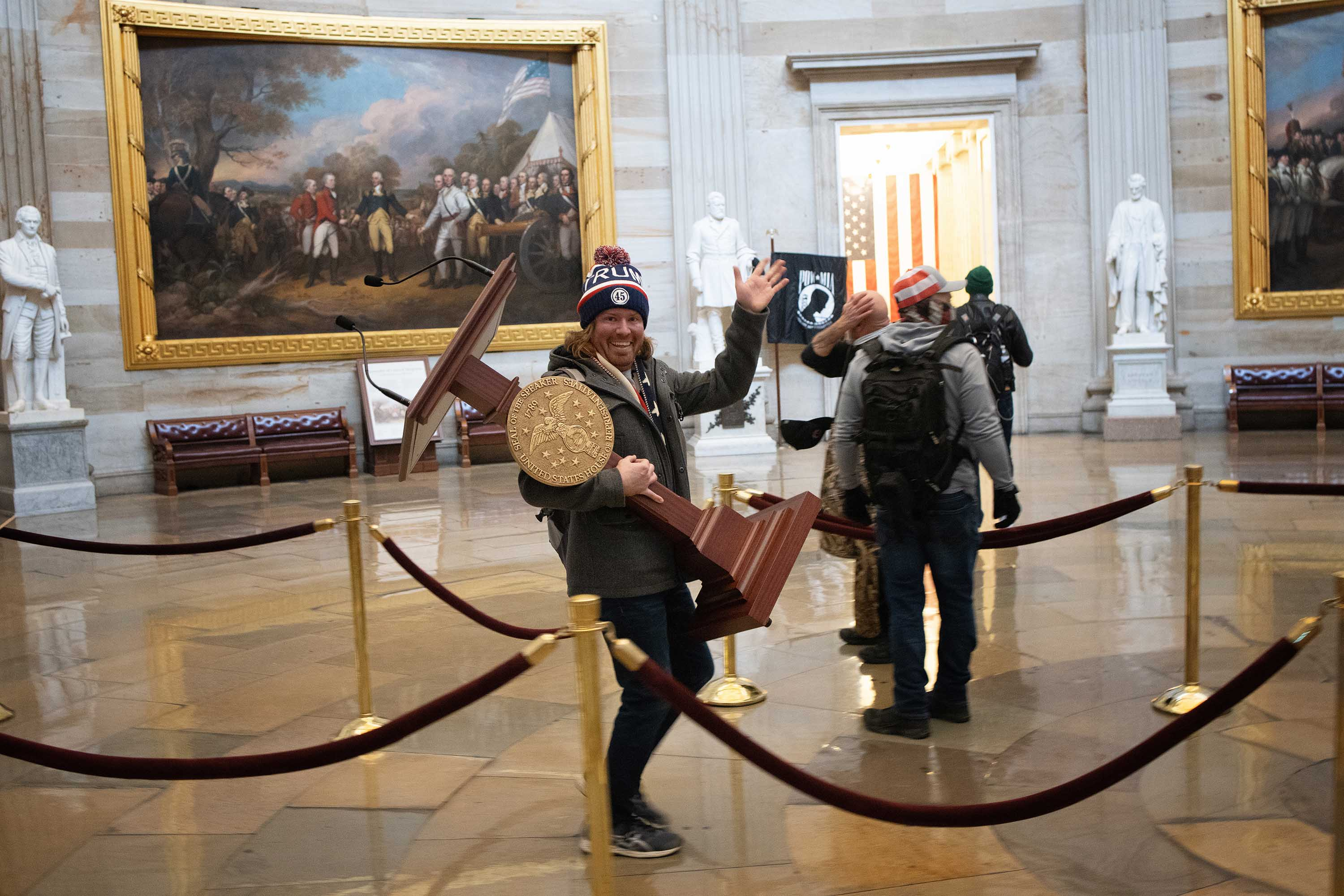 A pro-Donald Trump rioter, identified as Adam Johnson, carries the lectern of House Speaker Nancy Pelosi through the Capitol on January 6.