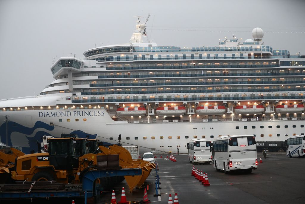Two buses arrive next to the Diamond Princess cruise ship, with people quarantined onboard due to fears of the new coronavirus, at the Daikaku Pier Cruise Terminal in Yokohama port on February 16, 2020