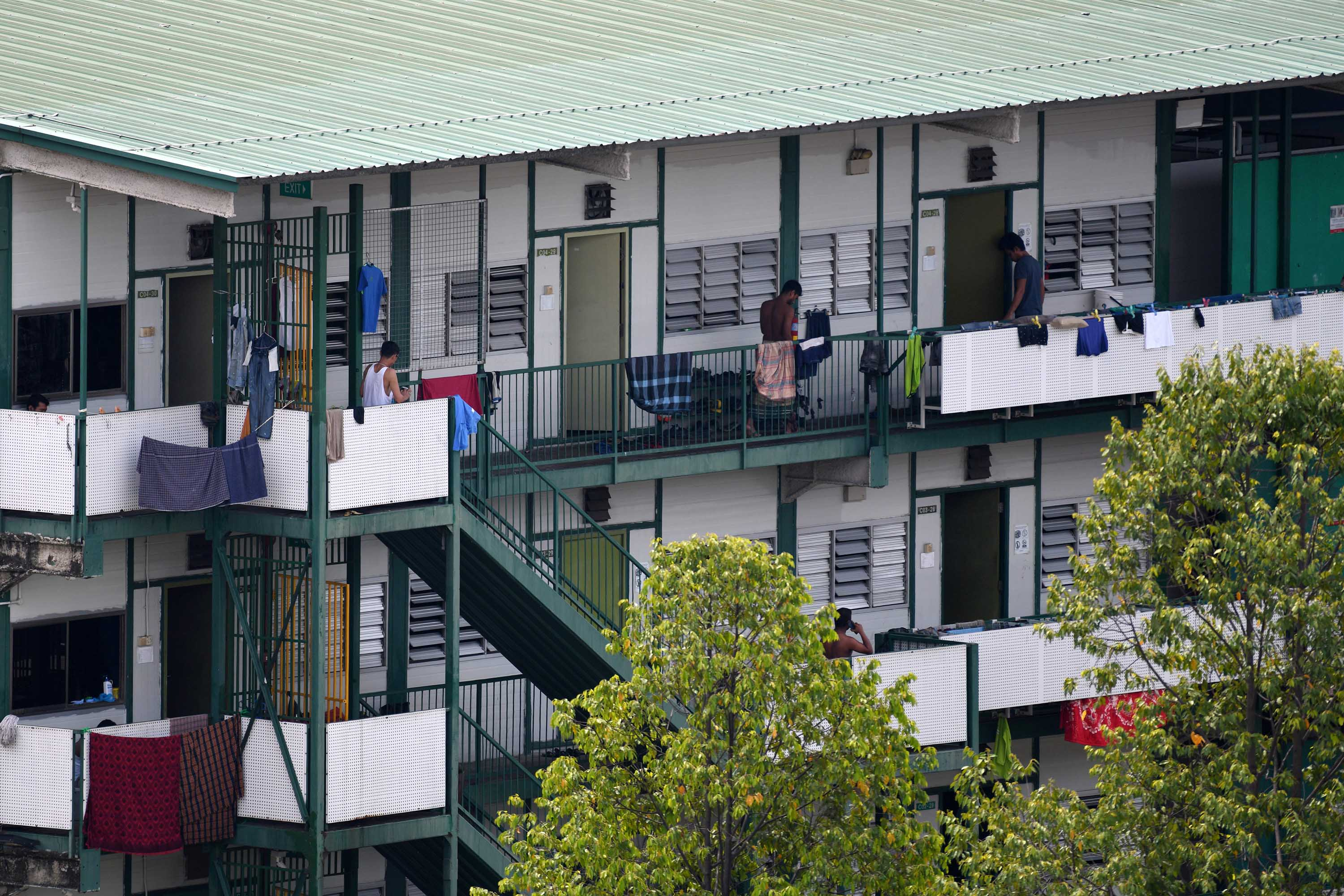 Men stand on the balcony of a dormitory used to house migrant workers in Singapore on April 17.