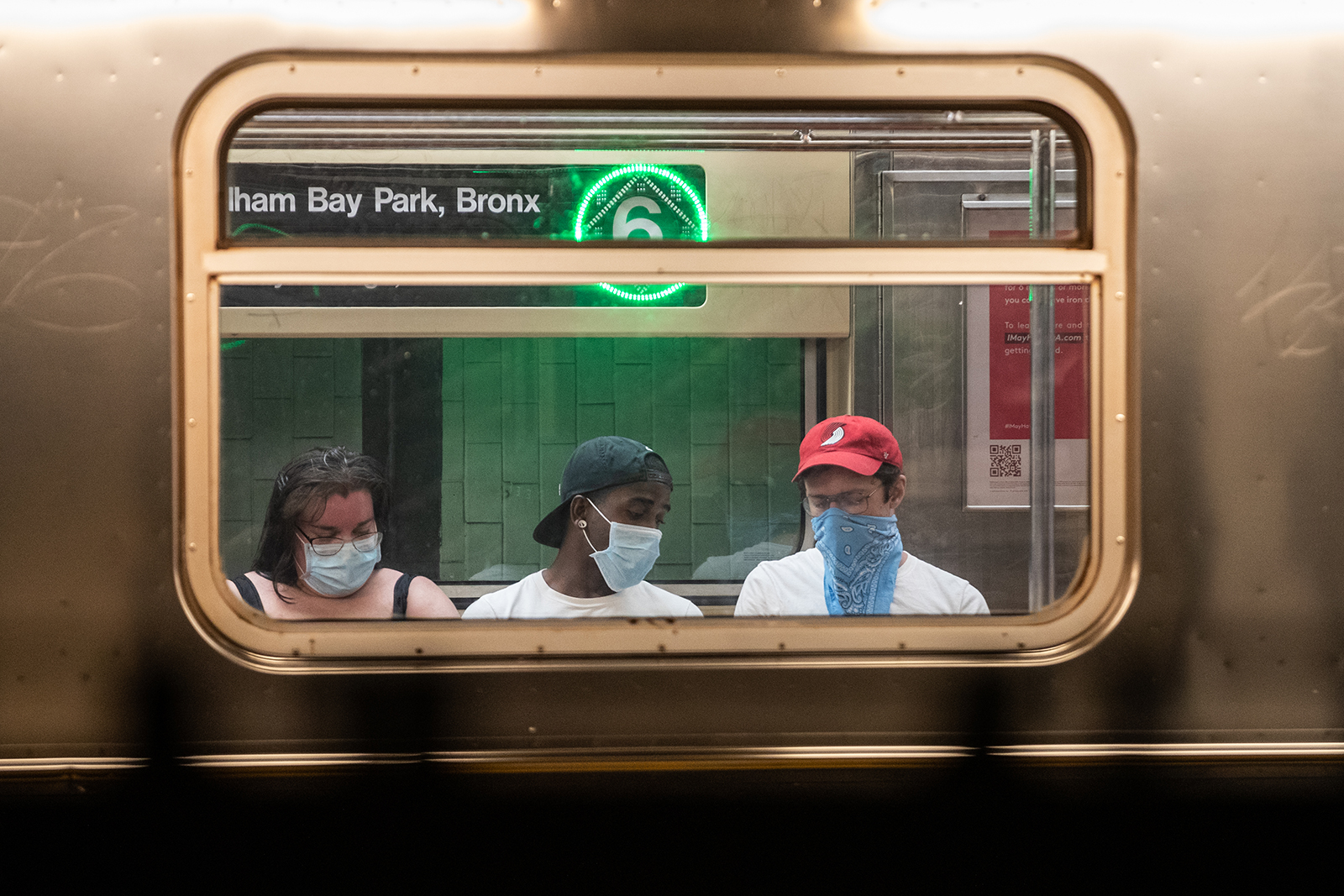 Passengers wearing protective masks ride the subway in New York, on June 10.