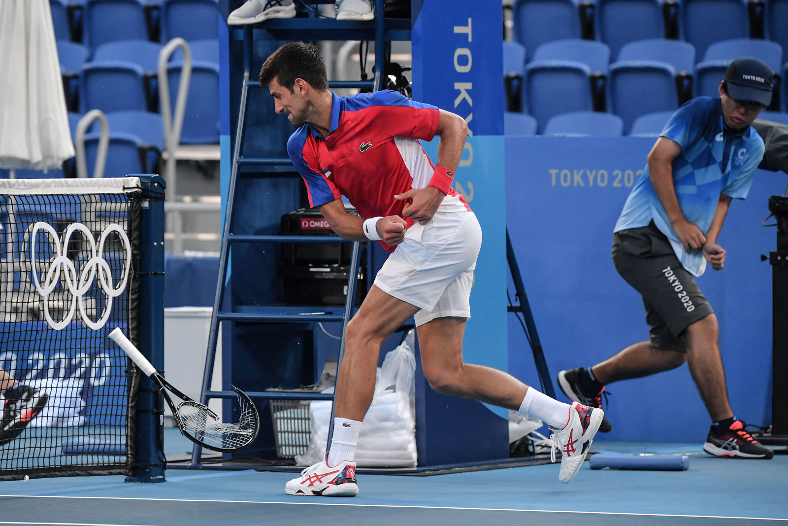 Novak Djokovic smashes his racket during his men's singles tennis match for the bronze medal against Pablo Carreno Busta.
