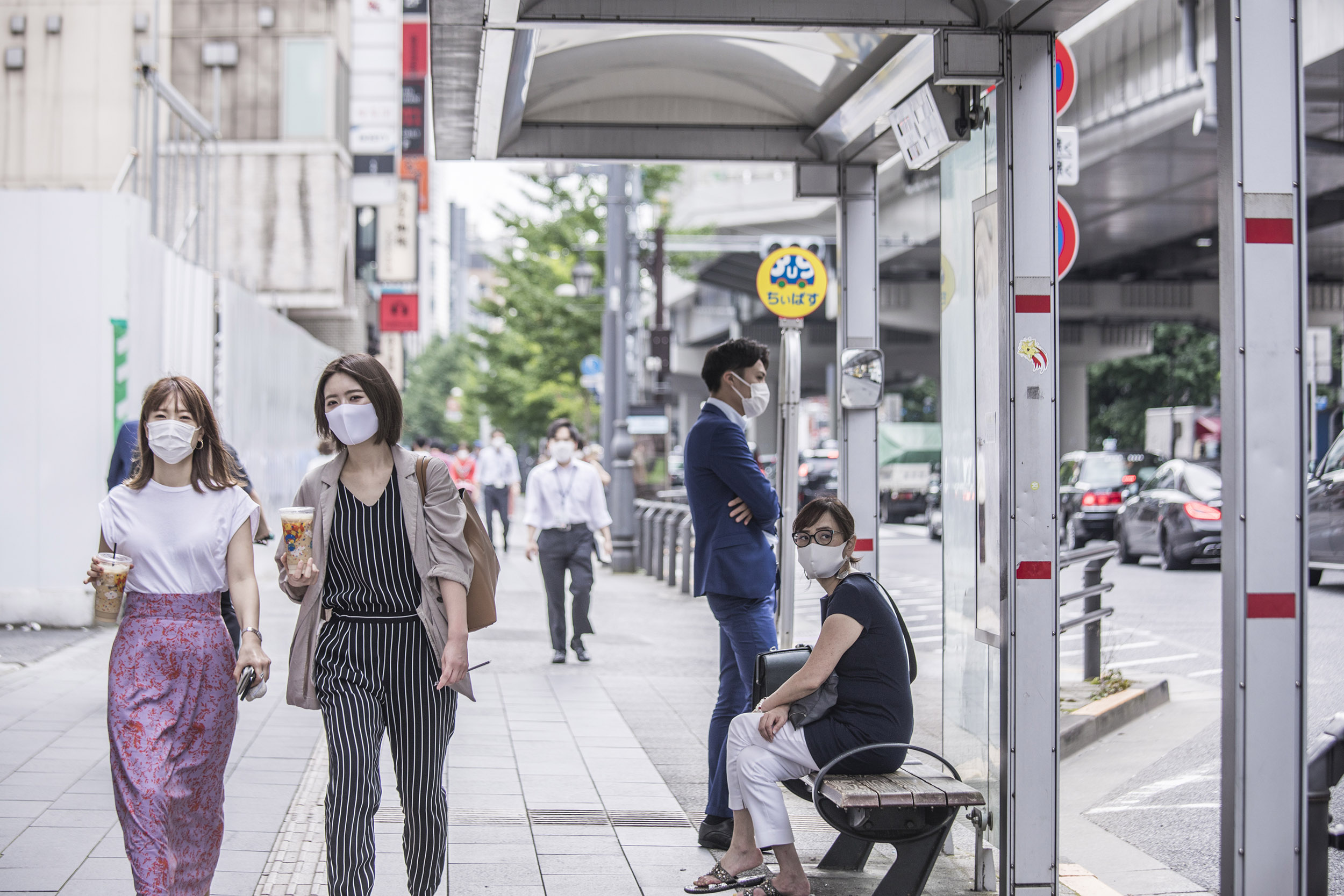 Pedestrians wearing protective masks walk along a sidewalk in Tokyo, Japan, on Thursday, July 30.