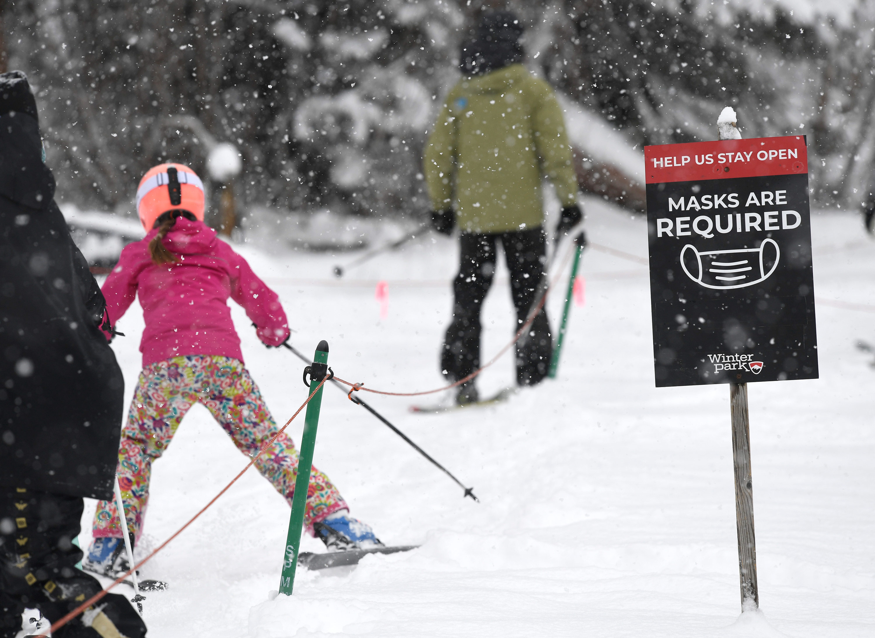 Skiers pass a mandatory face masks sign in Winter Park, Colorado, on February 13.