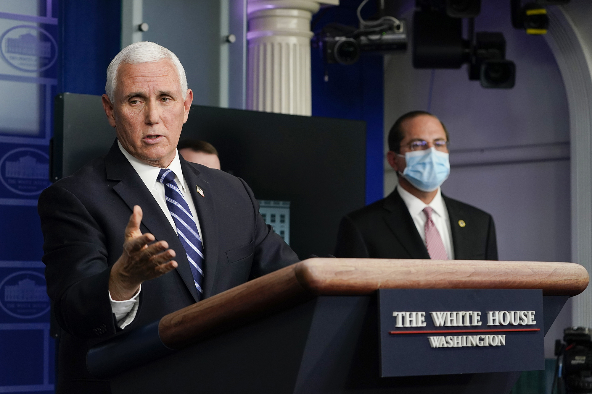 Health and Human Services Secretary Alex Azar, right, listens as Vice President Mike Pence speaks during a news conference with the coronavirus task force at the White House in Washington on Thursday.