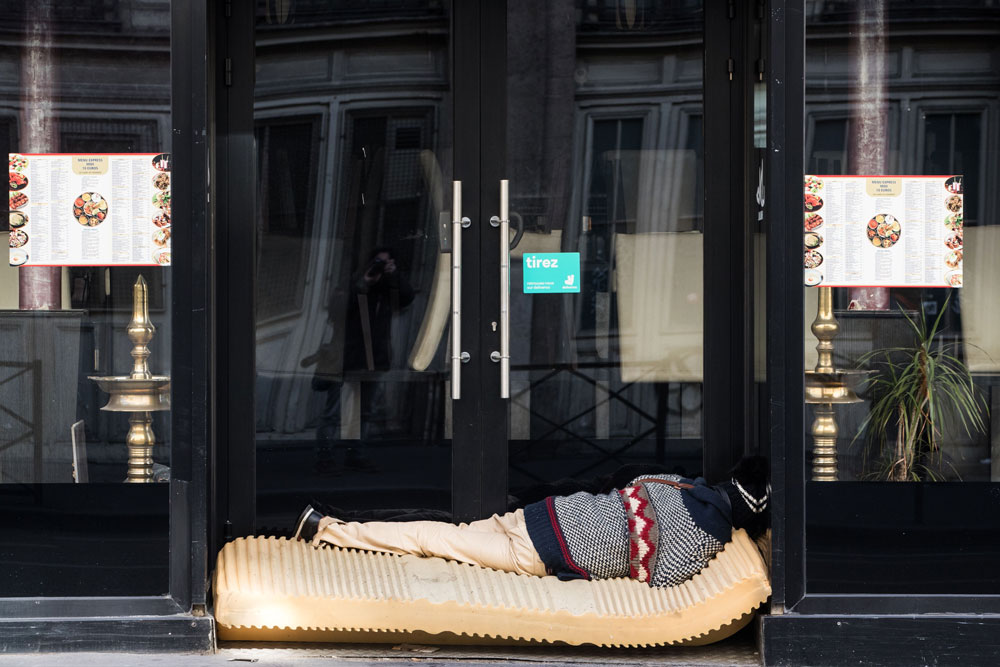 A homeless person lays in a doorway of a restaurant in Paris on March 31on the 15th day of the lockdown aimed at curbing the spread of the coronavirus.