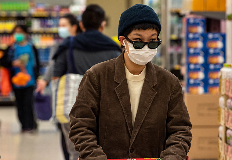 A shopper wearing a face mask and gloves while shopping in a Hong Kong supermarket, Wednesday, February 12.