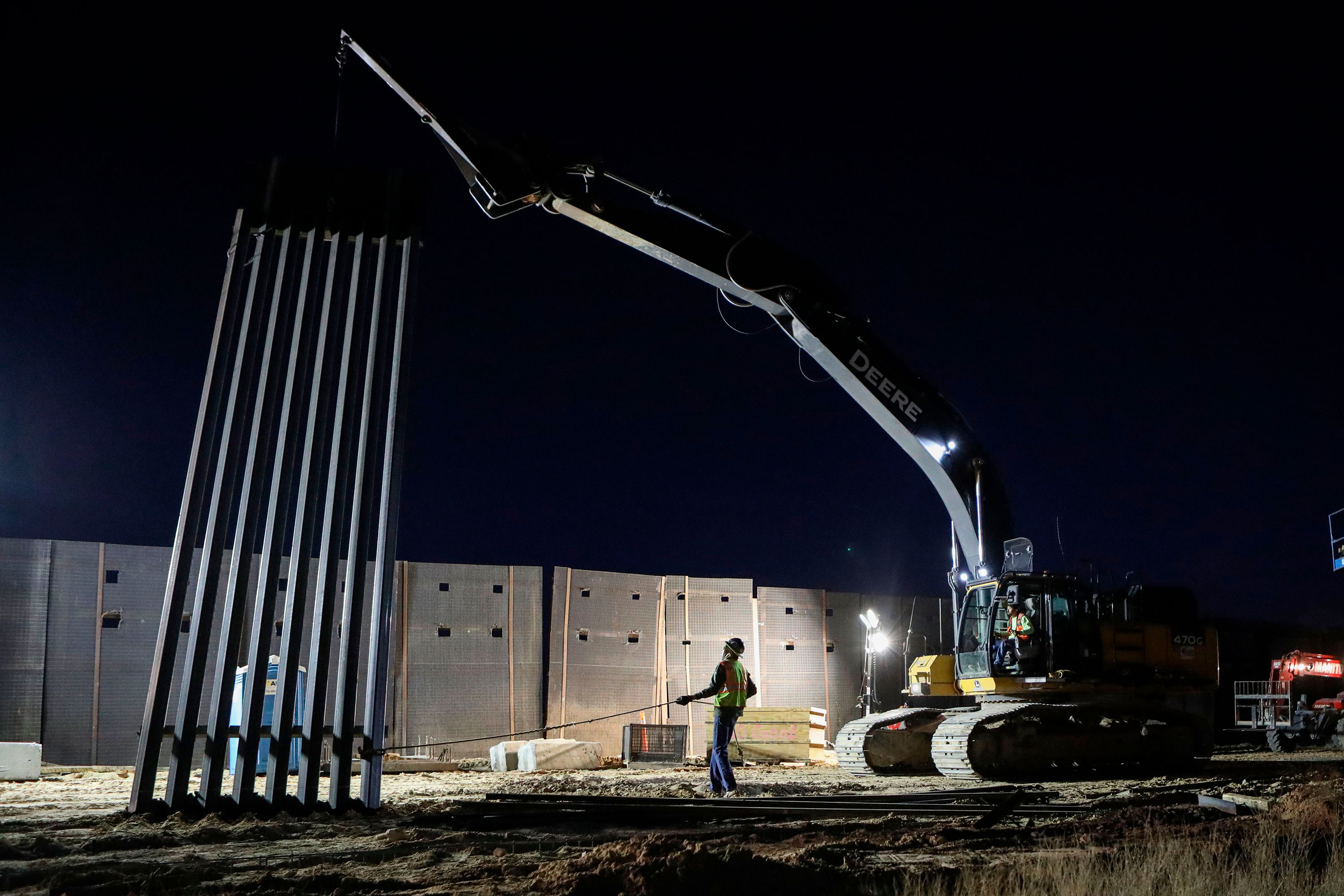 U.S. workers build the new 13-mile border wall construction project in the desert between Sunlad Park, New Mexico, and Ciudad Juarez, Mexico, on January 15.