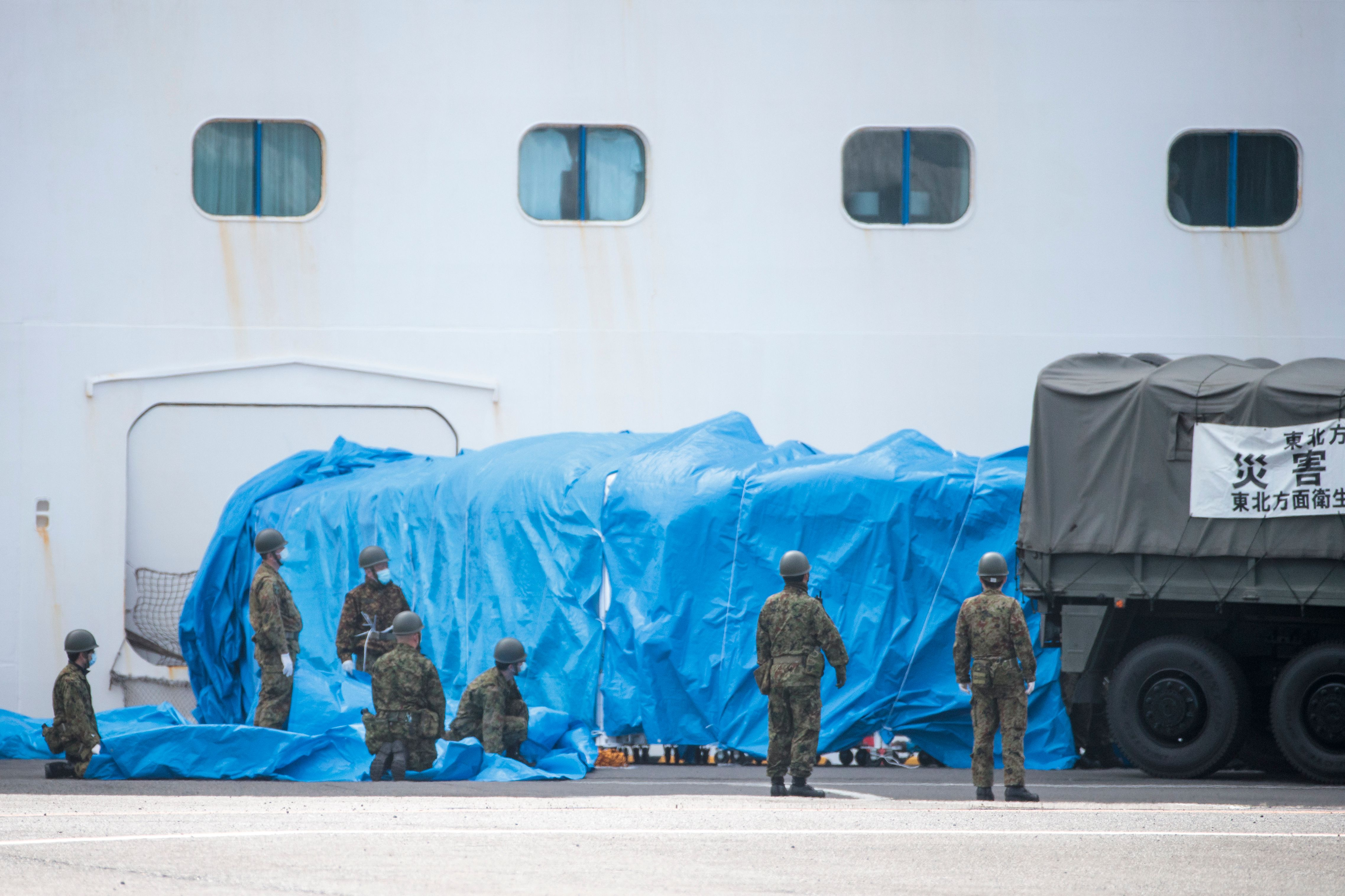Members of the Japan Self-Defense Forces attach a military vehicle to a gate of the Diamond Princess cruise ship.