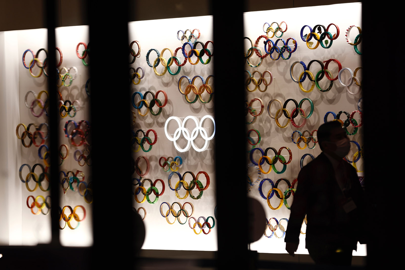 A man wearing a face mask walks past Olympic Rings at the Japan Olympic Museum in Tokyo on January 8, 2021.