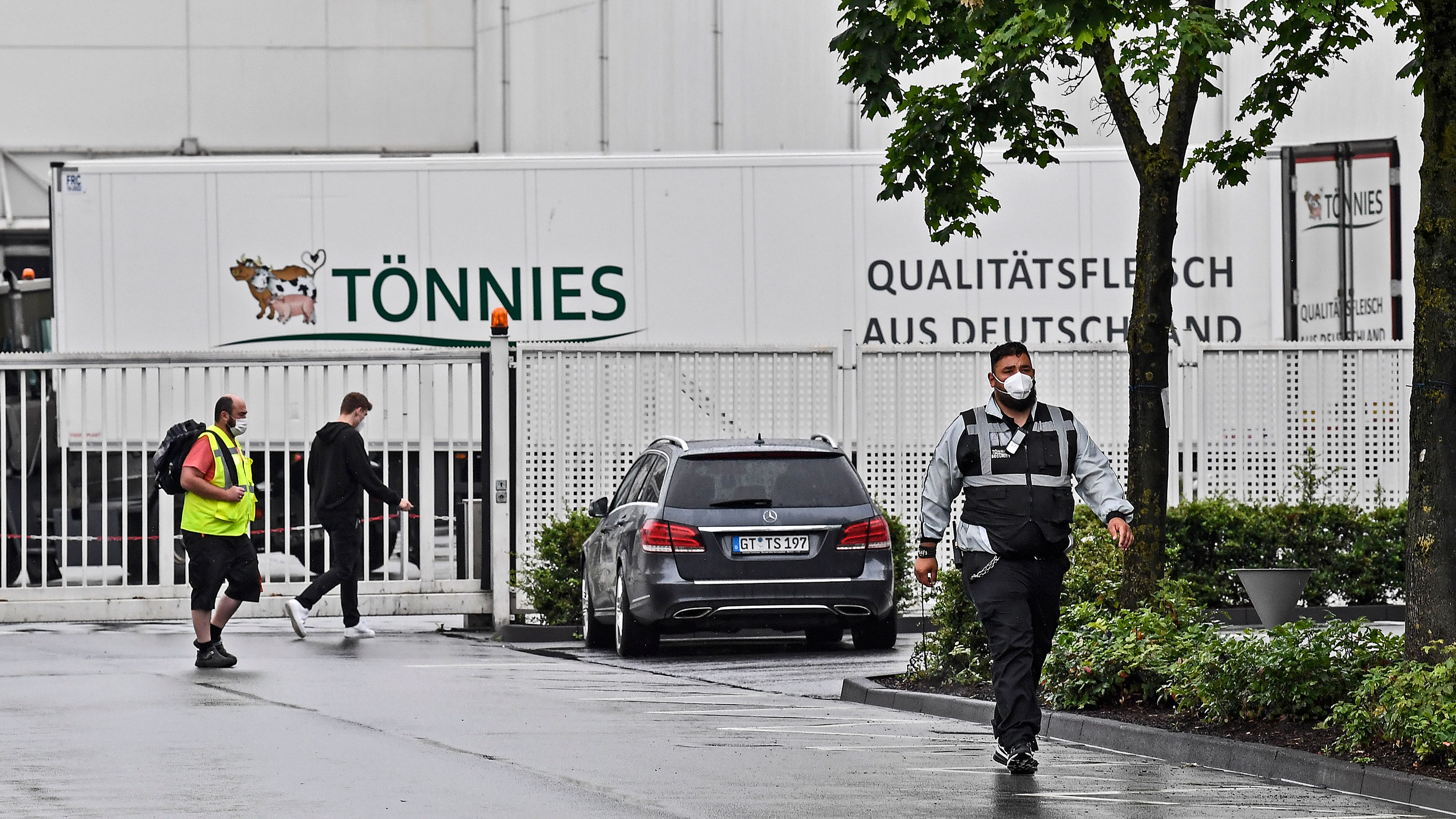 A member ofthe security walks in front of the Toennies meatpacking plant in Rheda-Wiedenbrueck, Germany, on June 18.