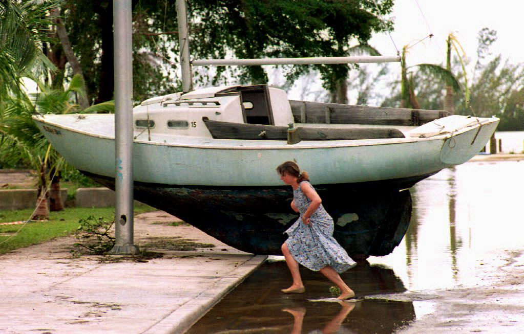 A woman jumps across a flooded street in Coconut Grove, Miami, on Aug 24, 1992, in front of a sailboat washed ashore by Hurricane Andrew.
