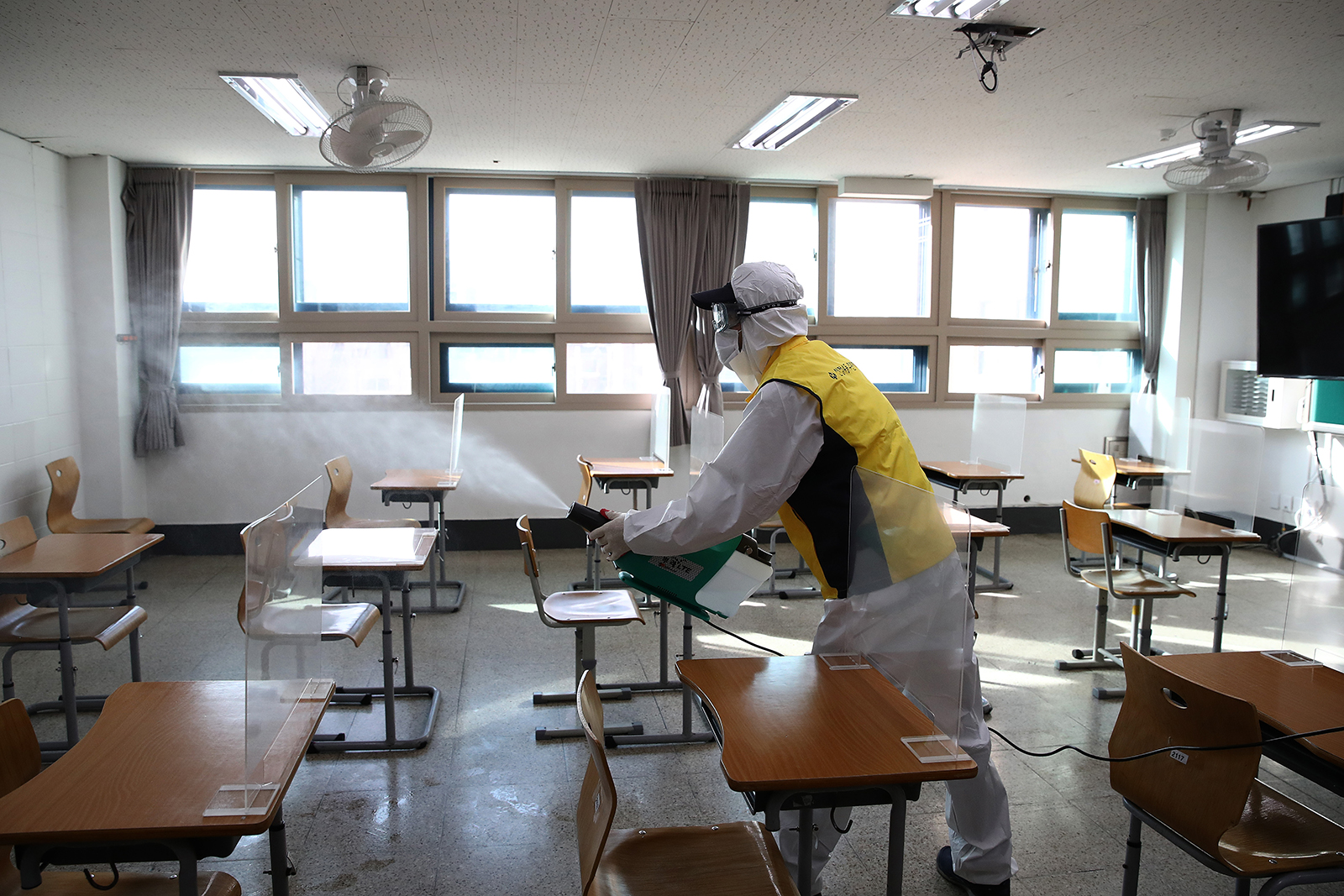 A disinfection worker sprays antiseptic solution in a classroom to prevent the spread of Covid-19 ahead of the annual college scholastic ability test at a YoungSang high school in Seoul on December 1.