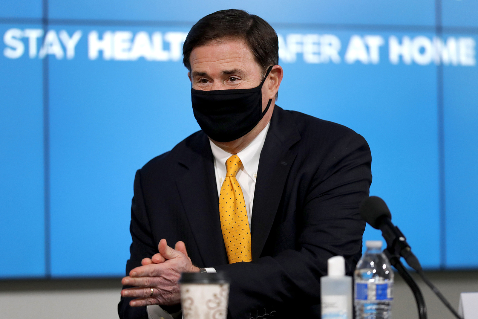 In this July 23, 2020 file photo, Arizona Republican Gov. Doug Ducey applies hand sanitizer prior to giving the latest Arizona coronavirus update during a news conference in Phoenix.