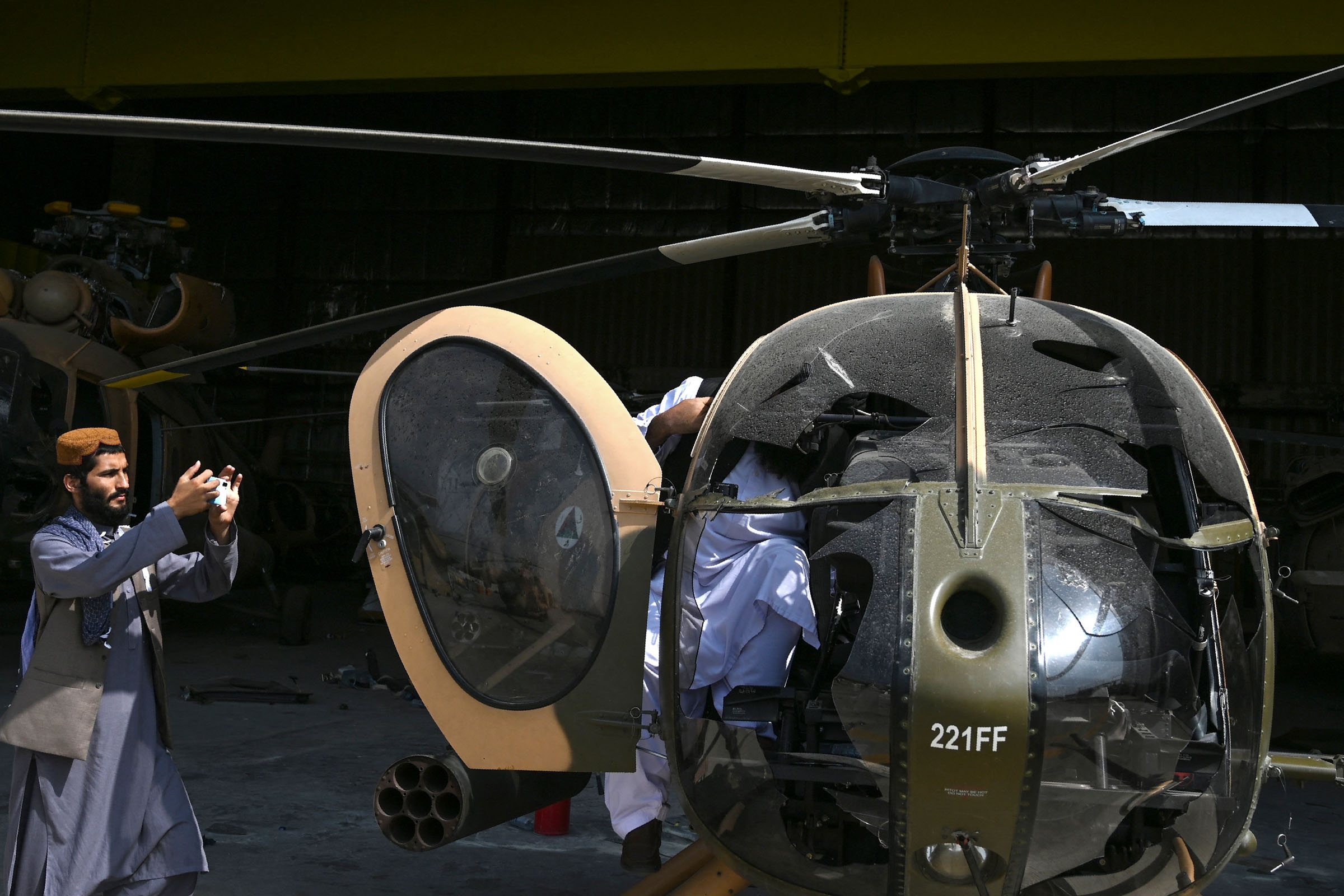 A Taliban fighter takes a picture of a damaged Afghan Air Forces MD 530 helicopter at Kabul airport.
