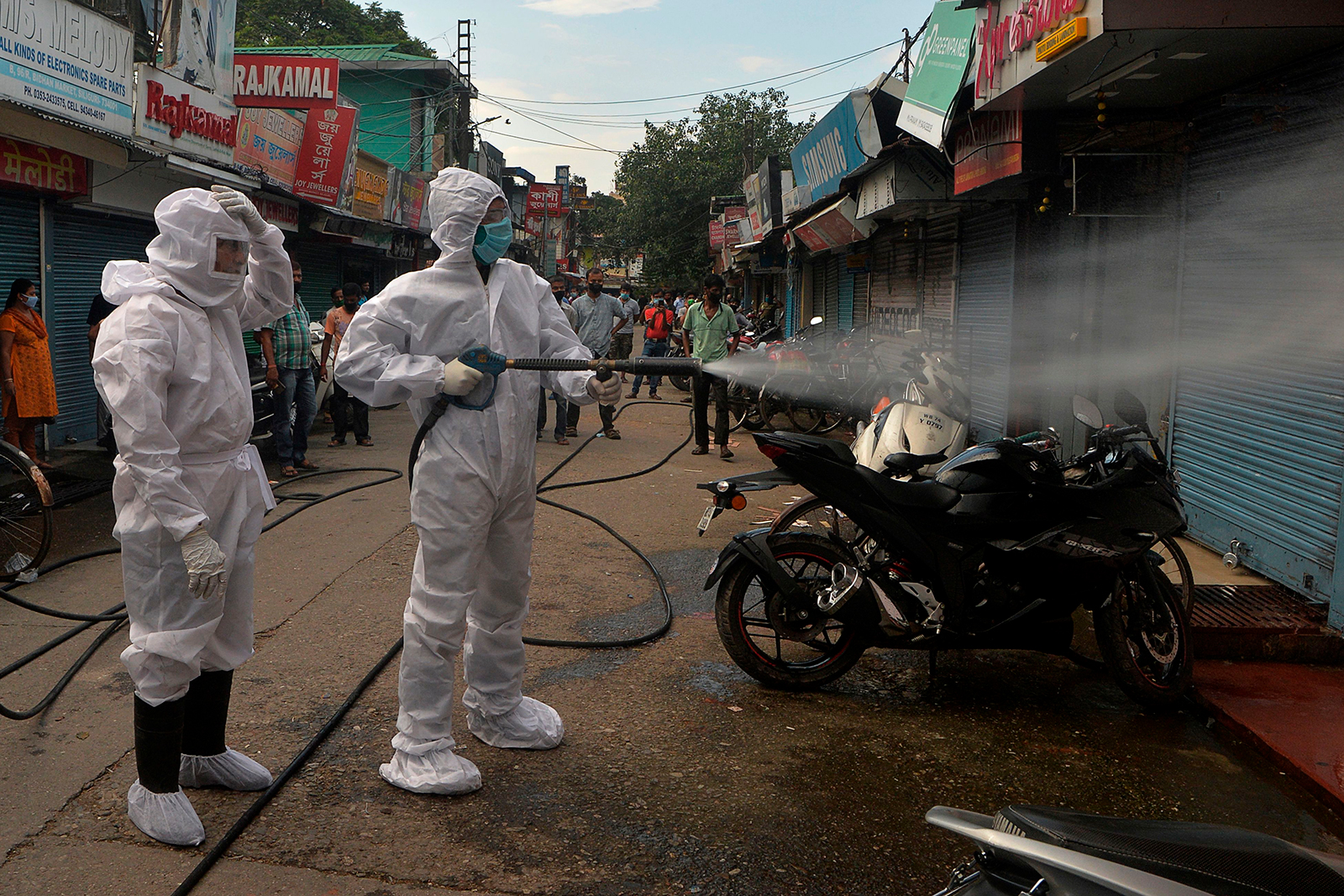 Firefighters wearing personal protective gear spray disinfectant in a closed market in Siliguri, India on June 22.