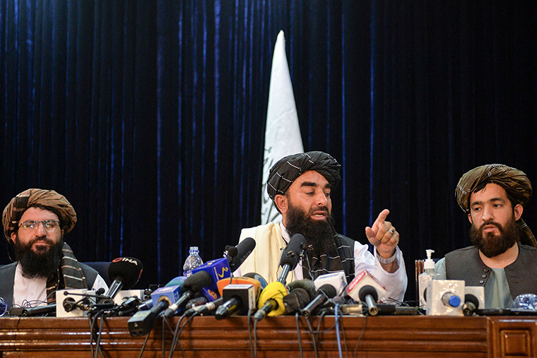Taliban spokesperson Zabihullah Mujahid, center, gestures as he addresses the first press conference in Kabul onTuesday, August 17.
