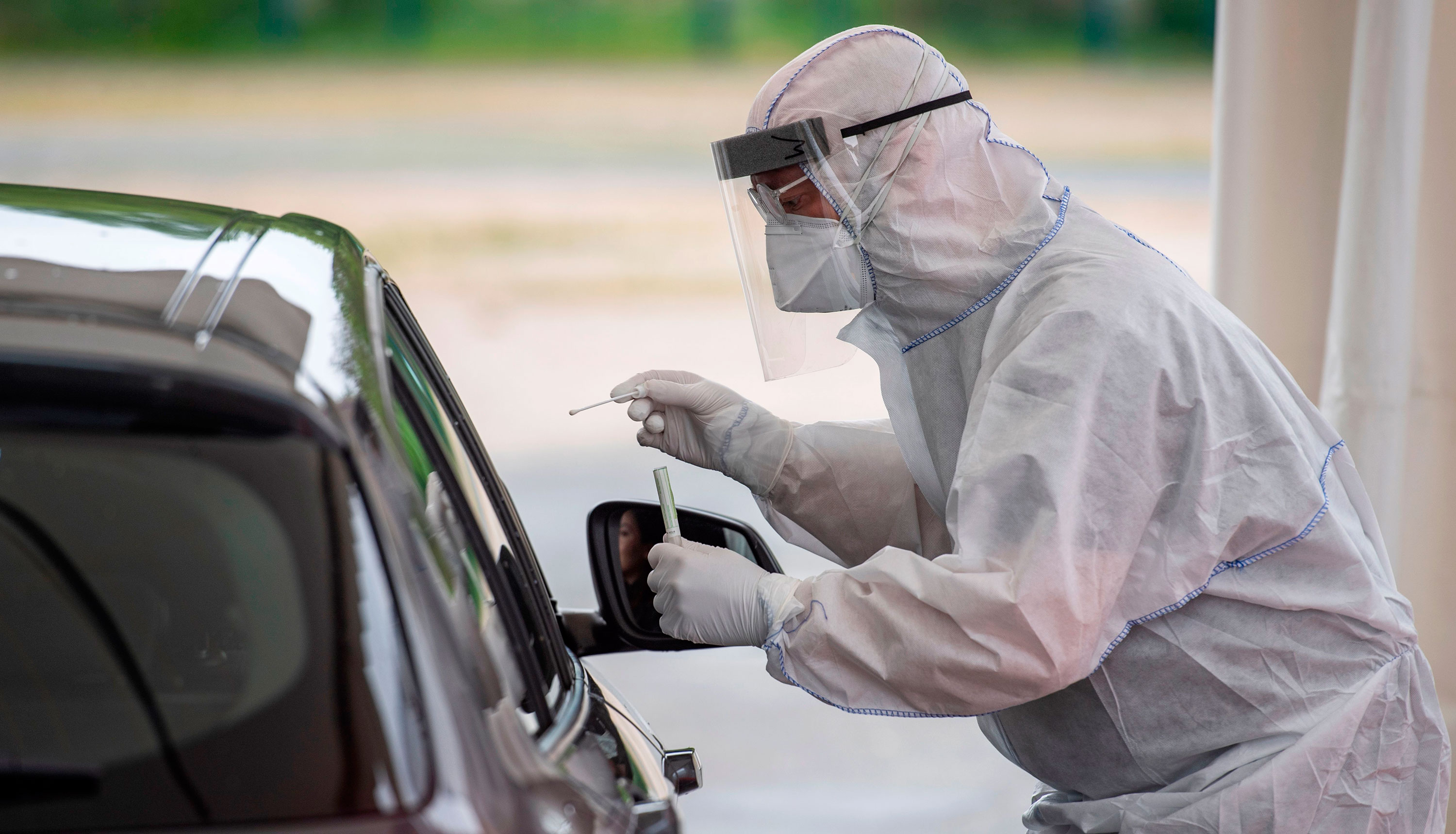 A doctor conducts a coronavirus test at a drive-thru testing site in Berlin, Germany, on April 30.