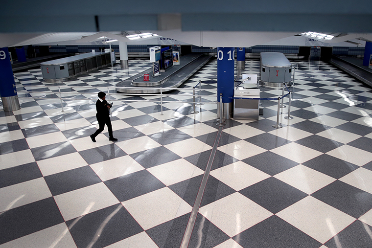 A worker walks through a baggage claim area at a nearly-empty O'Hare International Airport on April 2,  in Chicago.