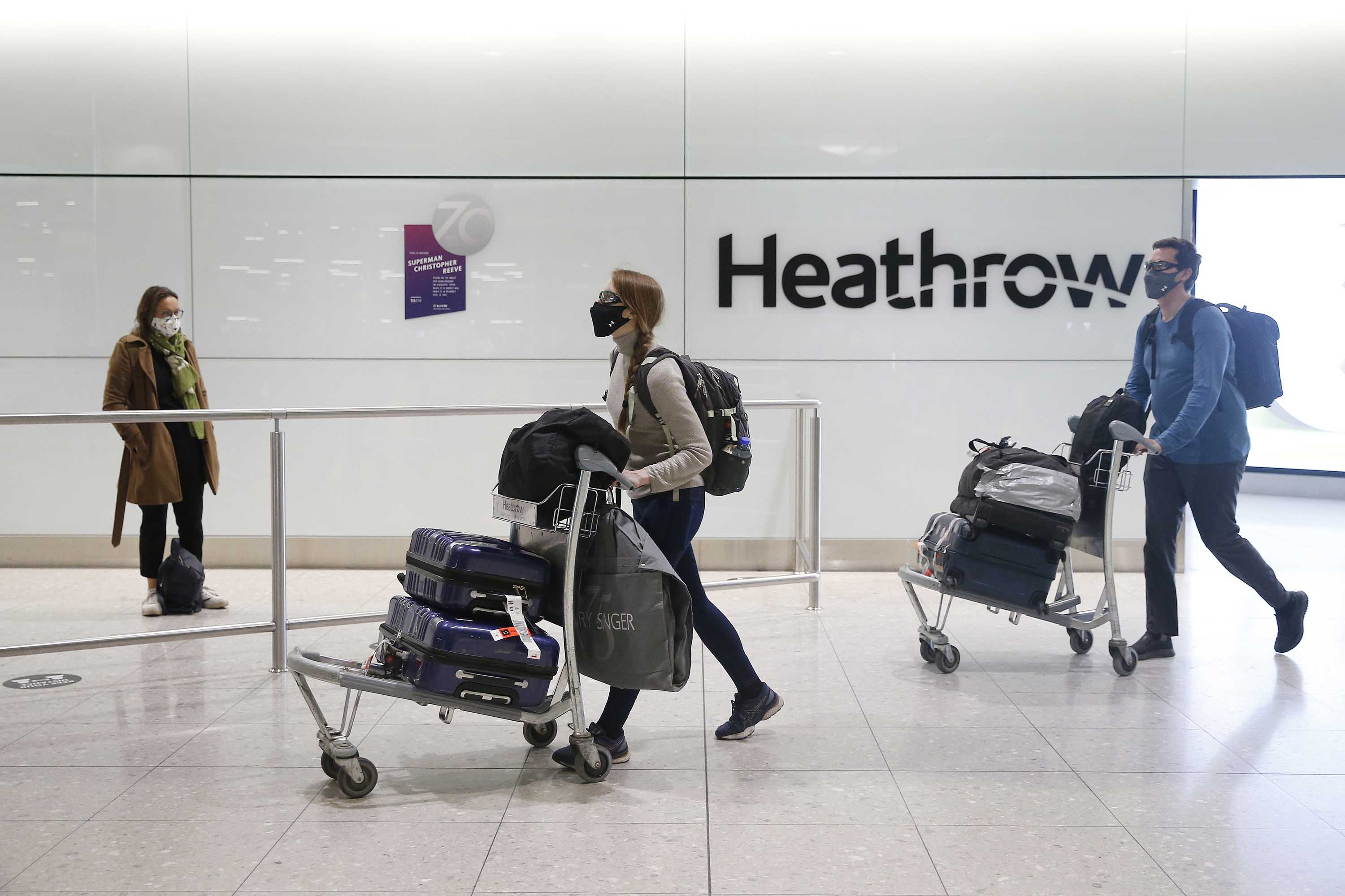 Travelers arrive at Heathrow Airport on January 30, in London, England.