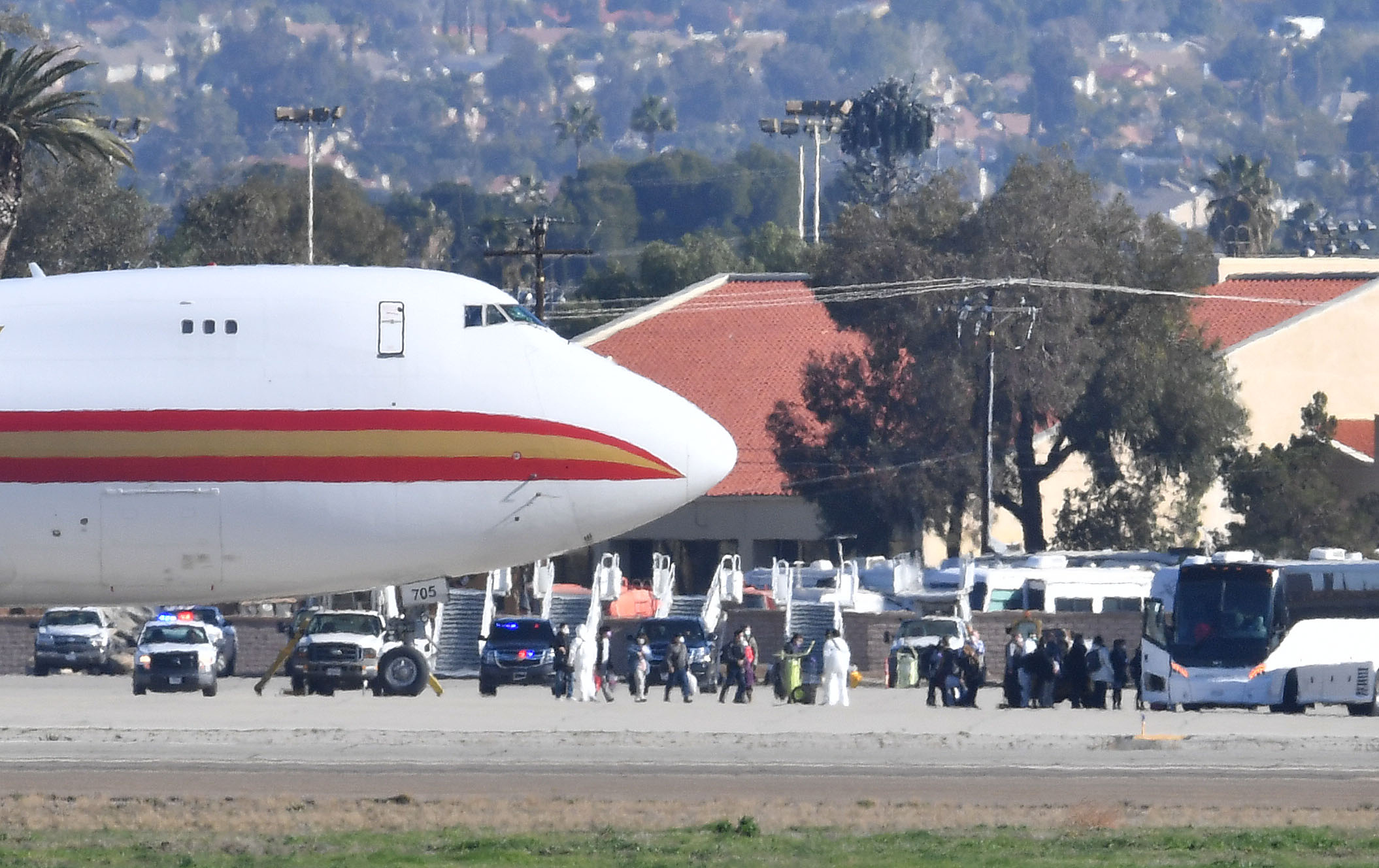 A team in white biohazard suits watch as some of the approximately 200 passengers walk to waiting buses upon arriving on a charter flight from Wuhan, China, after landing at March Air Reserve Base in Riverside, California, on Wednesday, January 29.