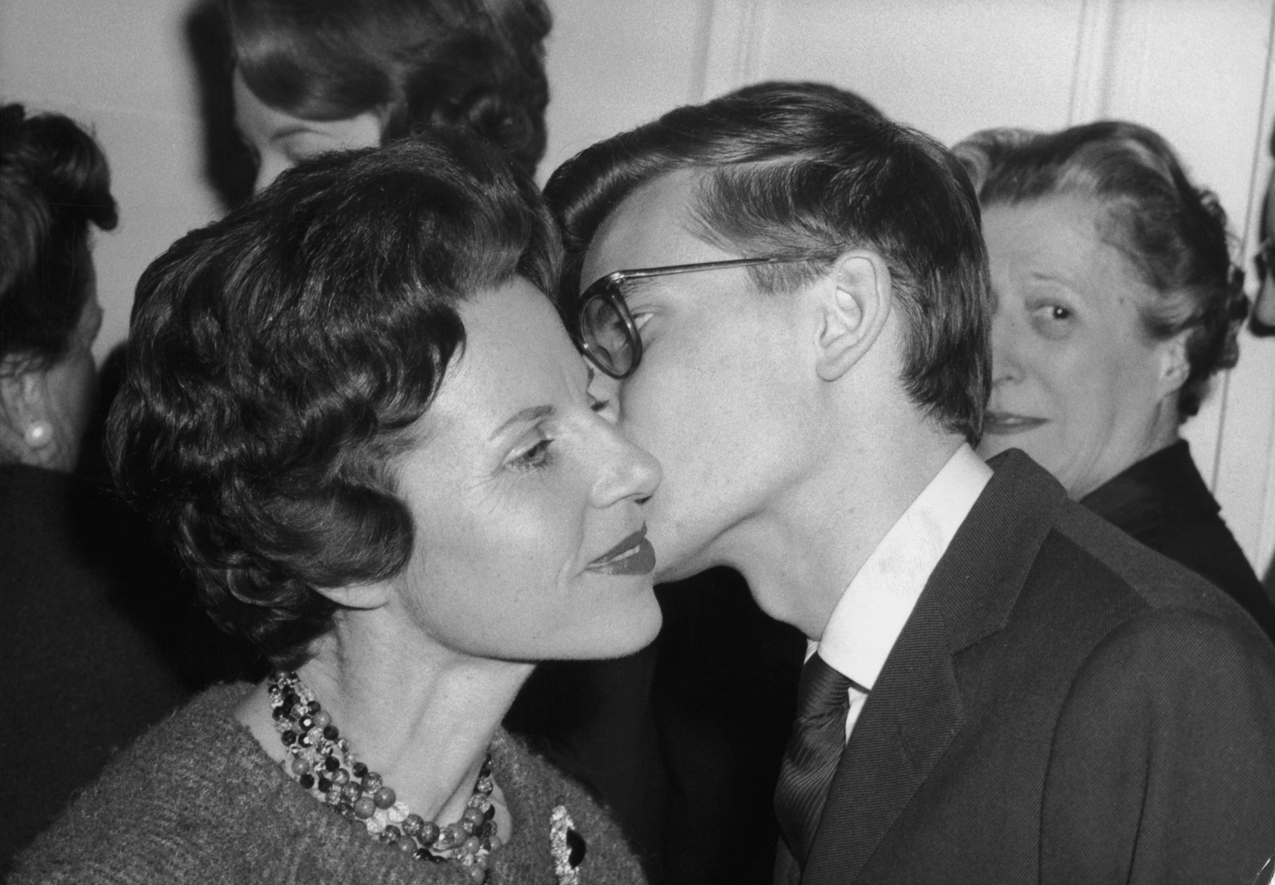 "The tradition of ""la bise"" involves kissing on the cheek, as demonstrated by the late French fashion designer Yves Saint Laurent as he greets his mother in Paris in 1959."