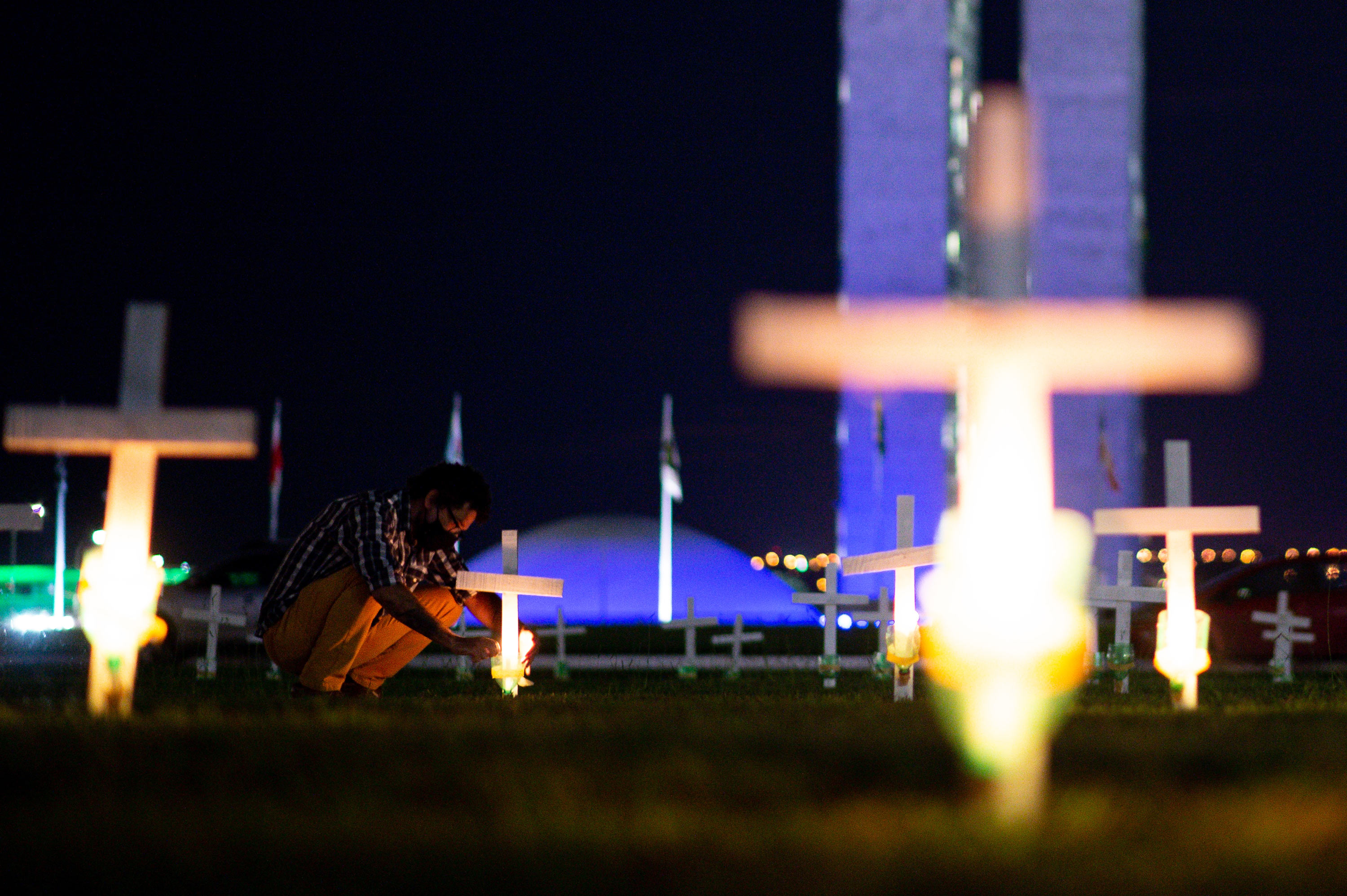 A person lights a candle in honor of the victims of the COVID-19 pandemic at the Brazilian Congress on April 27 in Brasilia, Brazil.