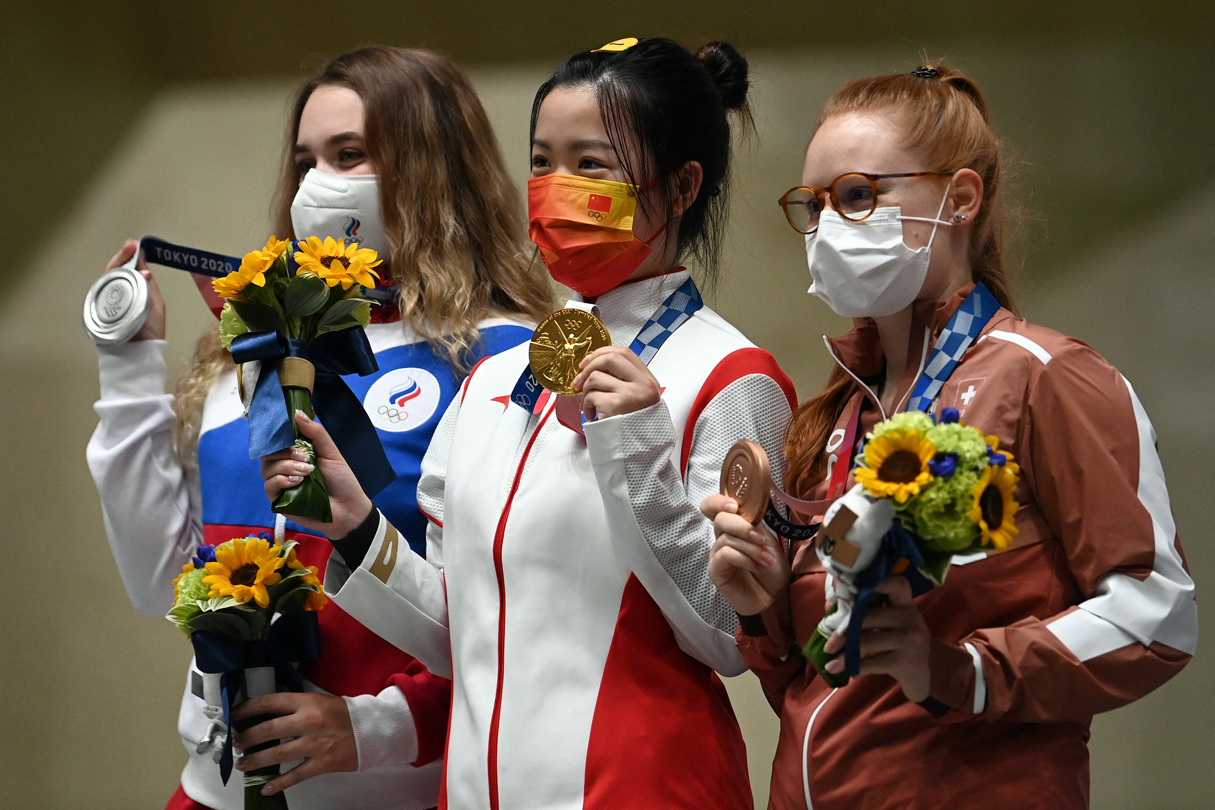Russia's Anastasiia Galashina, China's Yang Qian and Switzerland's Nina Christen pose with their medals after the women's 10m air rifle final on July 24.