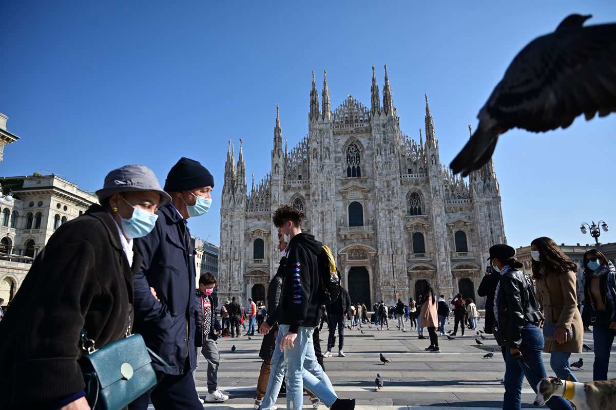 People wearing protective masks walk across the Piazza del Duomo in Milan on October 17. Italy's government has made it mandatory to wear face protection outdoors, in an attempt to counter the spread of the coronavirus.